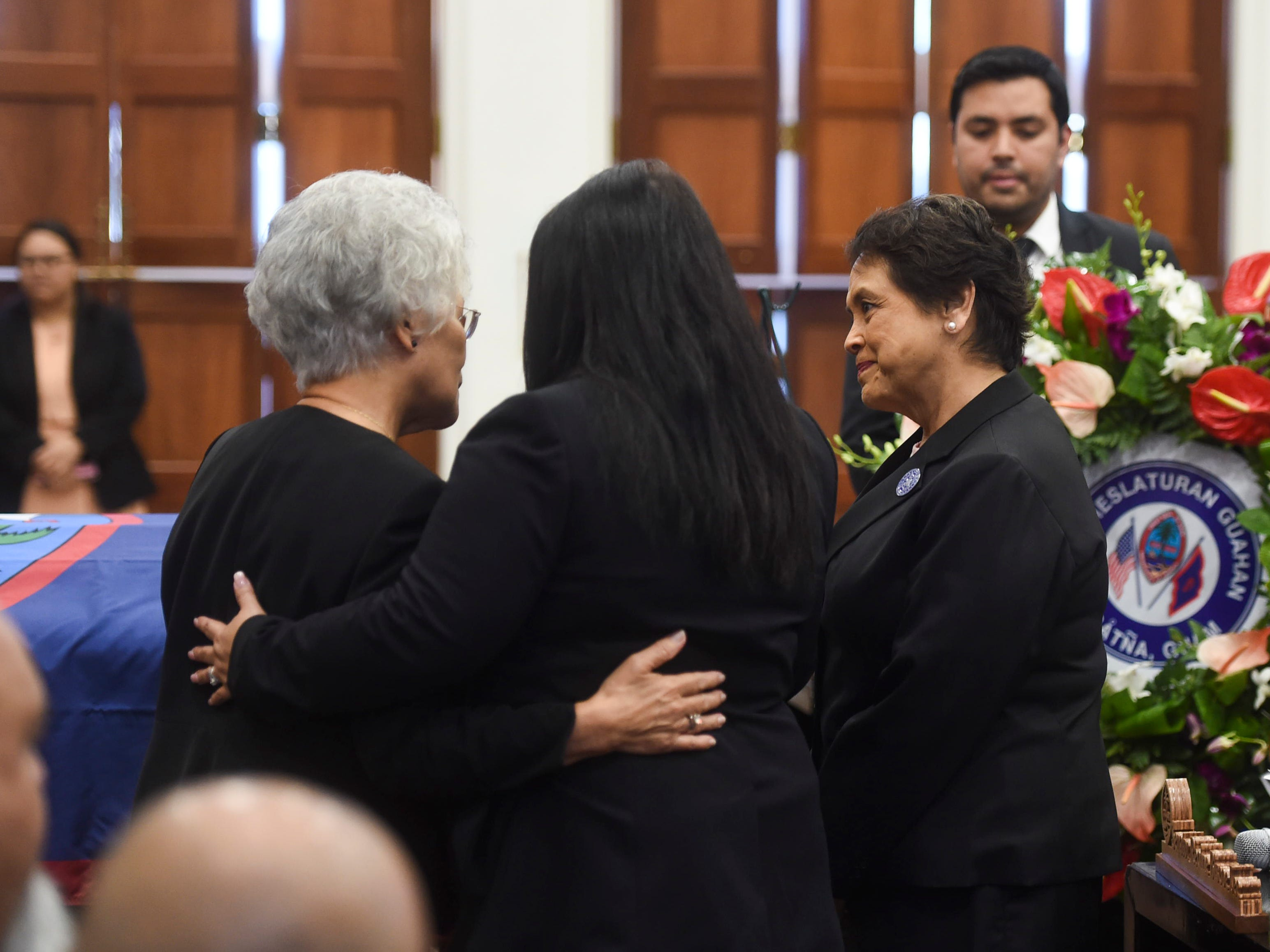 "Antonia Gumataotao, left, is consoled by Speaker Tina Muna Barnes, center, and Gov. Lou Leon Guerrero during the state memorial service of her husband and former Piti Mayor Vicente ""Ben"" Gumataotao, at the Guam Congress Building on Jan. 12, 2019."