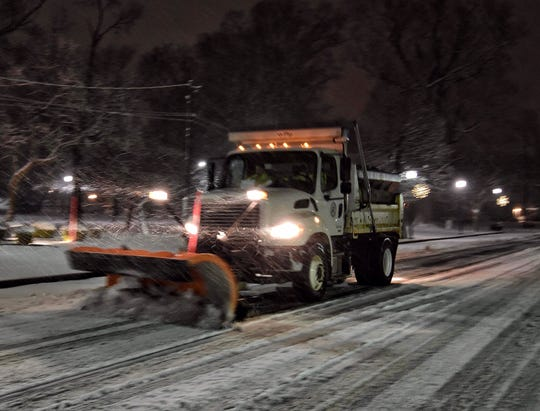 A City of Henderson truck plows Water Street Friday as the snow continues to fall.