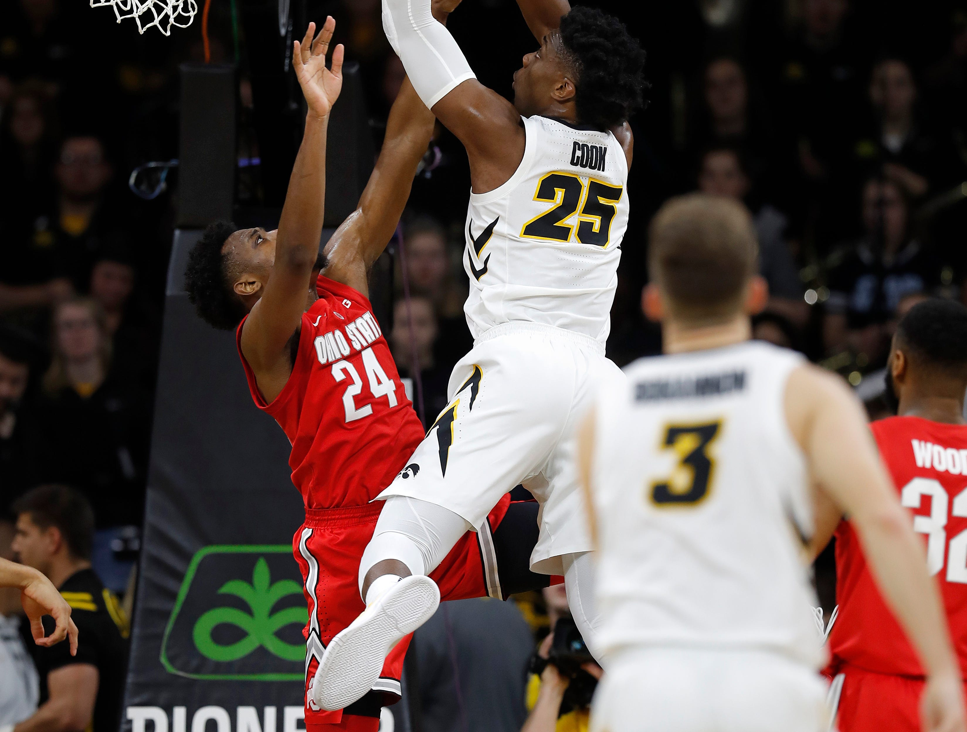 Iowa forward Tyler Cook, center, finds a basket as he is fouled by Ohio State forward Andre Wesson, left, during the first half of an NCAA college basketball game, Saturday, Jan. 12, 2019, in Iowa City, Iowa.