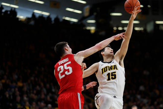 Ohio State forward Kyle Young, left, and Iowa forward Ryan Kriener, right, battle for a rebound during the first half of an NCAA college basketball game, Saturday, Jan. 12, 2019, in Iowa City, Iowa.