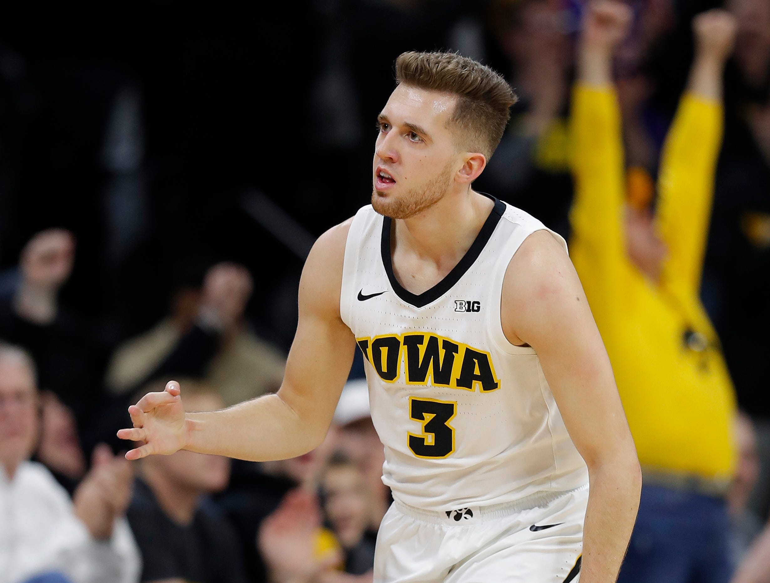 Iowa guard Jordan Bohannon celebrates a 3-point basket against Ohio State during the first half of an NCAA college basketball game, Saturday, Jan. 12, 2019, in Iowa City, Iowa.
