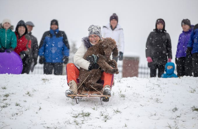 Cara Peggs holds her poodle Gershwin on a sled run at Butler University on a day where 5-7 inches of snow is expected to fall in Central Indiana, Indianapolis, Saturday, Jan. 12, 2019.