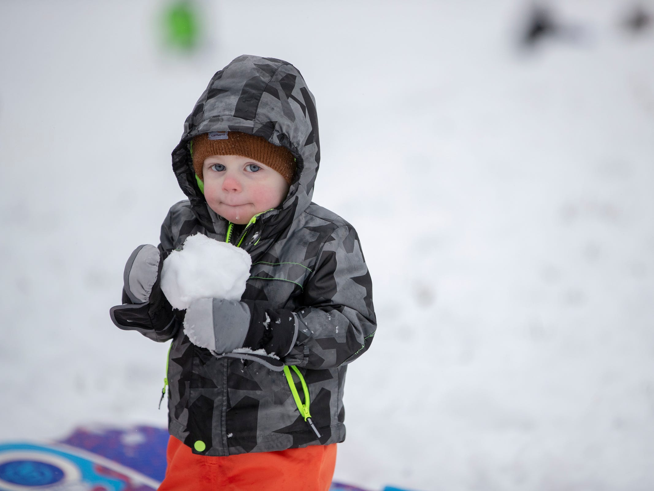 Bobby Jennings IV, 2, holds a snowball as he sleds with his parents and two sisters at Butler University on a day where 5-7 inches of snow is expected to fall in Central Indiana, Indianapolis, Saturday, Jan. 12, 2019.