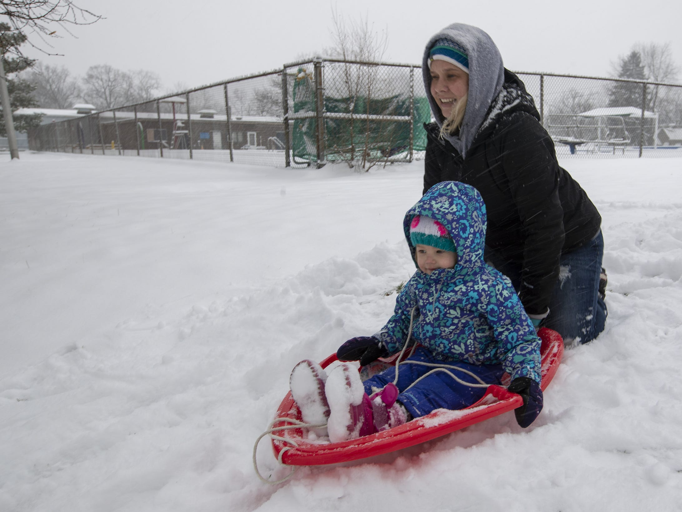 Libby Duggan pushes daughter Lucy Duggan, 3, as they sled at Ellenberger Park on a day where 5-7 inches of snow is expected to fall in Central Indiana, Indianapolis, Saturday, Jan. 12, 2019.