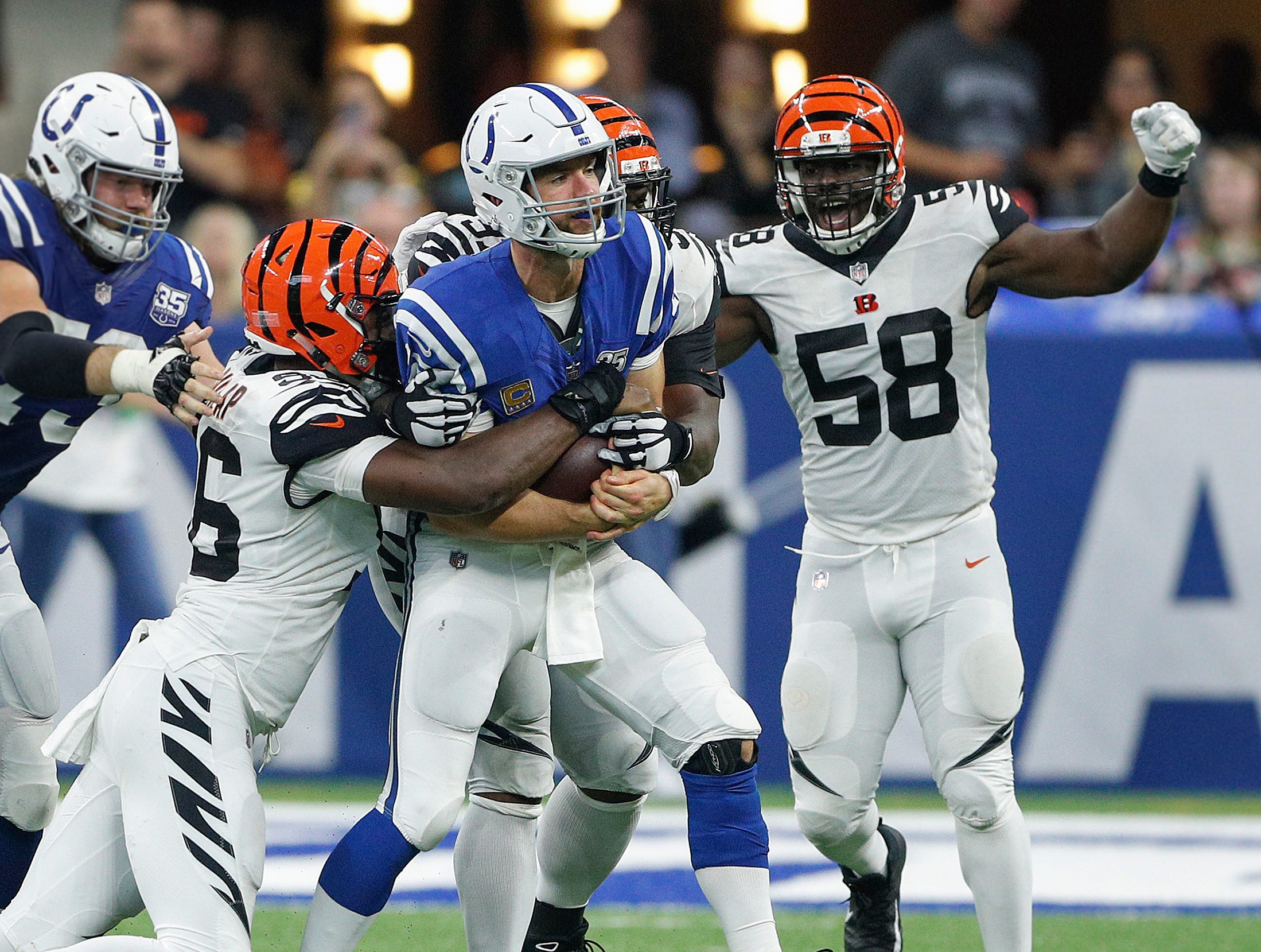 Indianapolis Colts quarterback Andrew Luck (12) is sacked by Cincinnati Bengals defensive end Carlos Dunlap (96) and  defensive end Al-Quadin Muhammad (97) in the second half of their game at Lucas Oil Stadium on Sept. 9, 2018. The Indianapolis Colts lost to the Cincinnati Bengals 34-23.