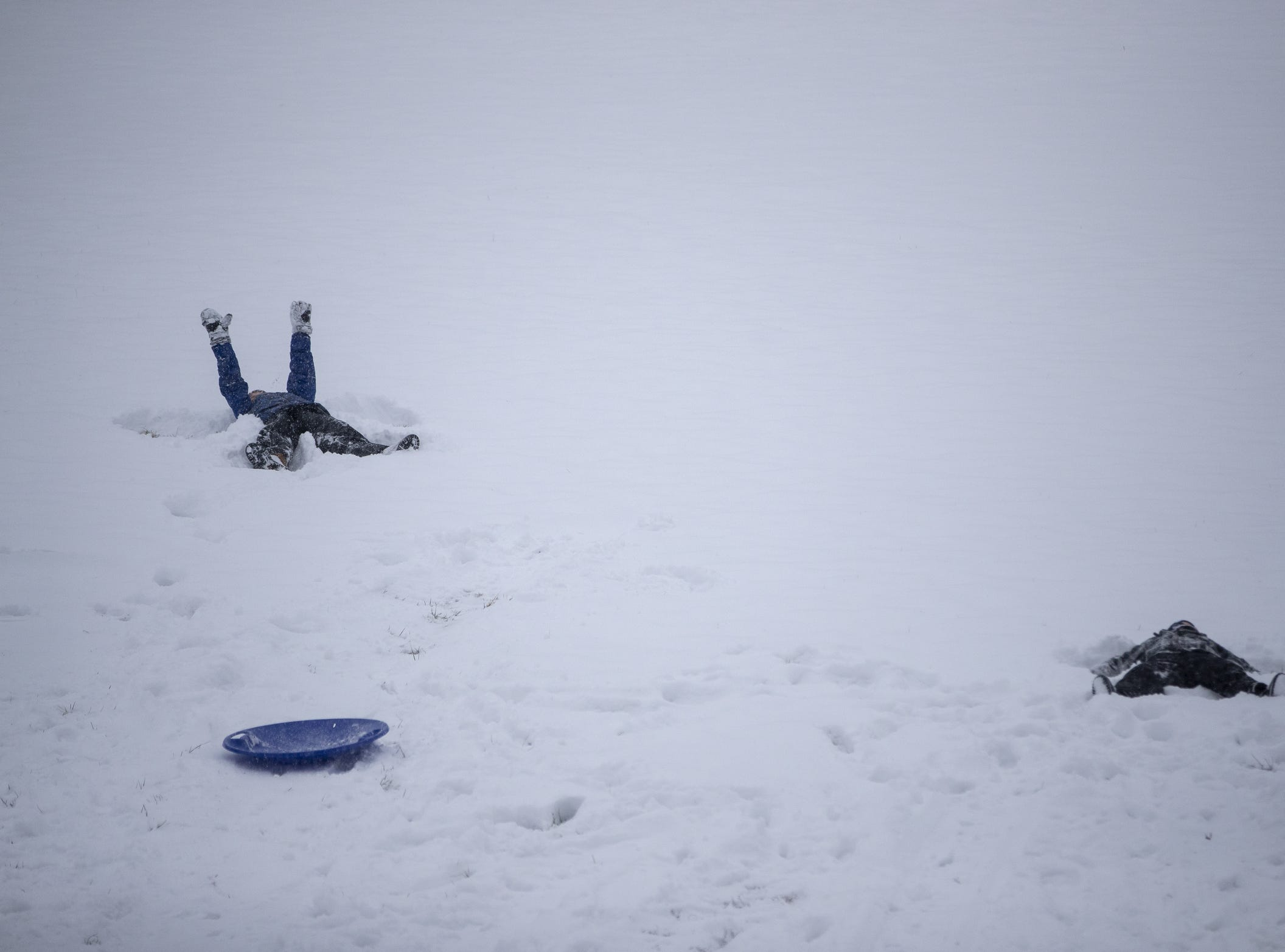 Kids make snow angels in Ellenberger Park on a day where 5-7 inches of snow is expected to fall in Central Indiana, Indianapolis, Saturday, Jan. 12, 2019.