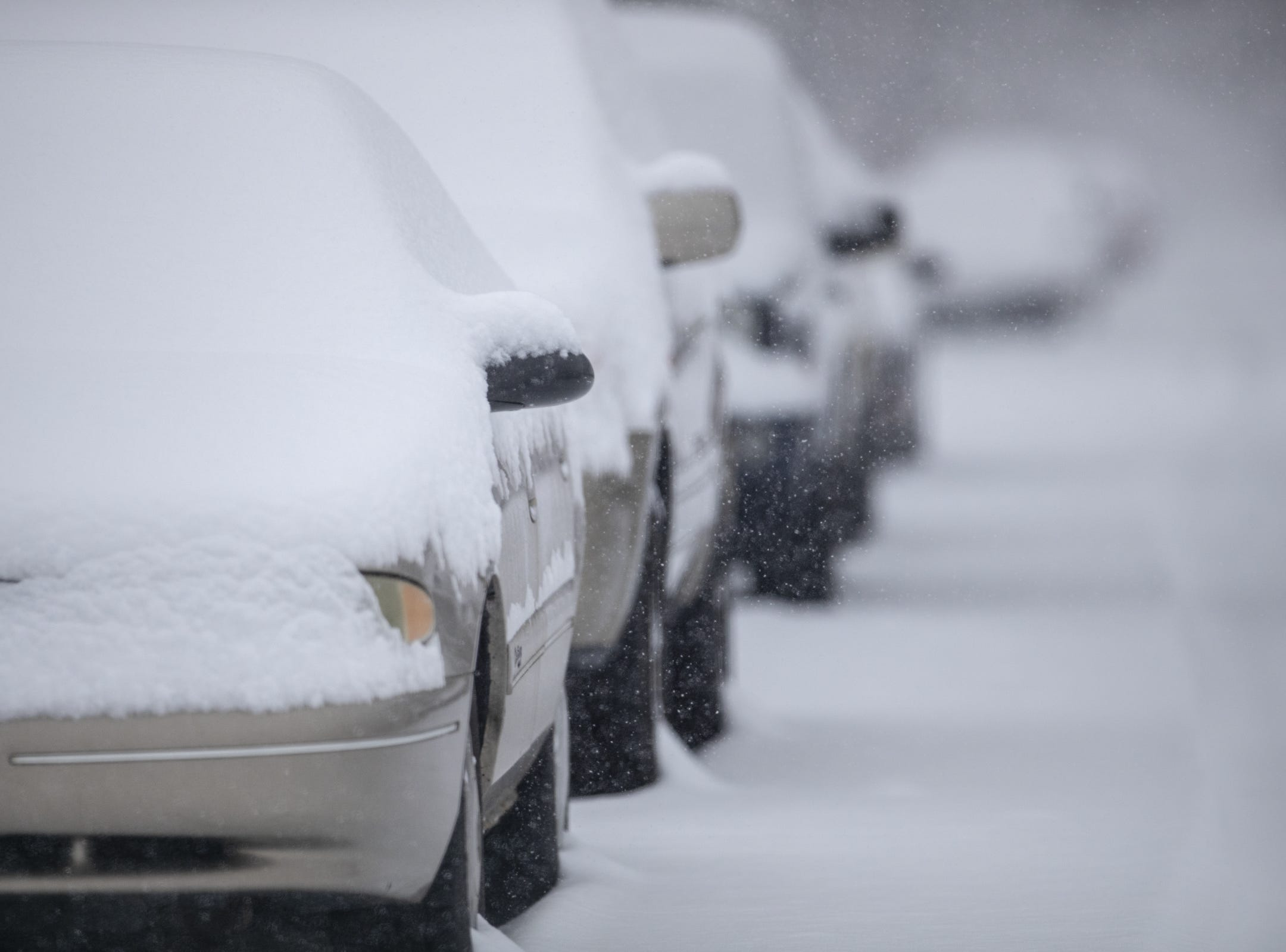 Snow-covered cars on the city's east side on a day where 5-7 inches of snow is expected to fall in Central Indiana, Indianapolis, Saturday, Jan. 12, 2019.
