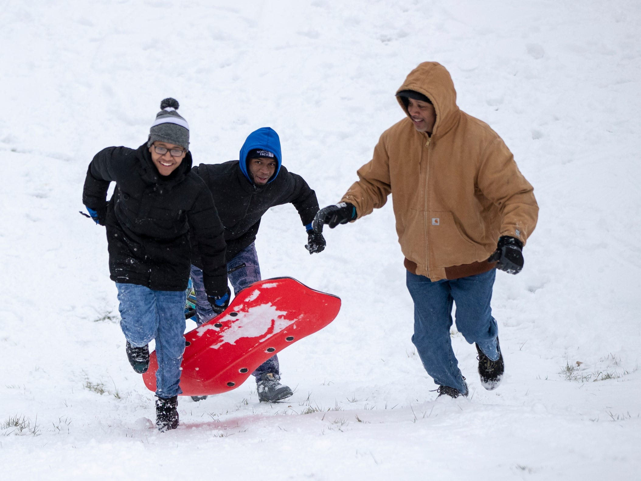 Damon Scott II (left), 15, friend Jamal Marshall, 17, and Scott's father Damon Scott, sled at Butler University on a day where 5-7 inches of snow is expected to fall in Central Indiana, Indianapolis, Saturday, Jan. 12, 2019.