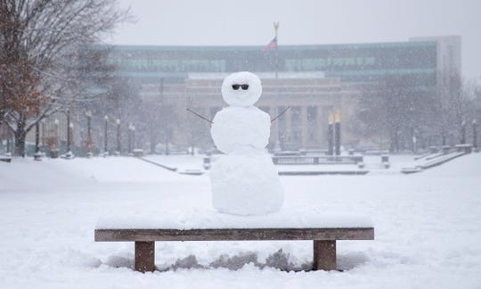 A snowman complete with shades, sits on a bench at Obelisk Square downtown, on a day where 5-7 inches of snow is expected to fall in Central Indiana, Indianapolis, Saturday, Jan. 12, 2019.