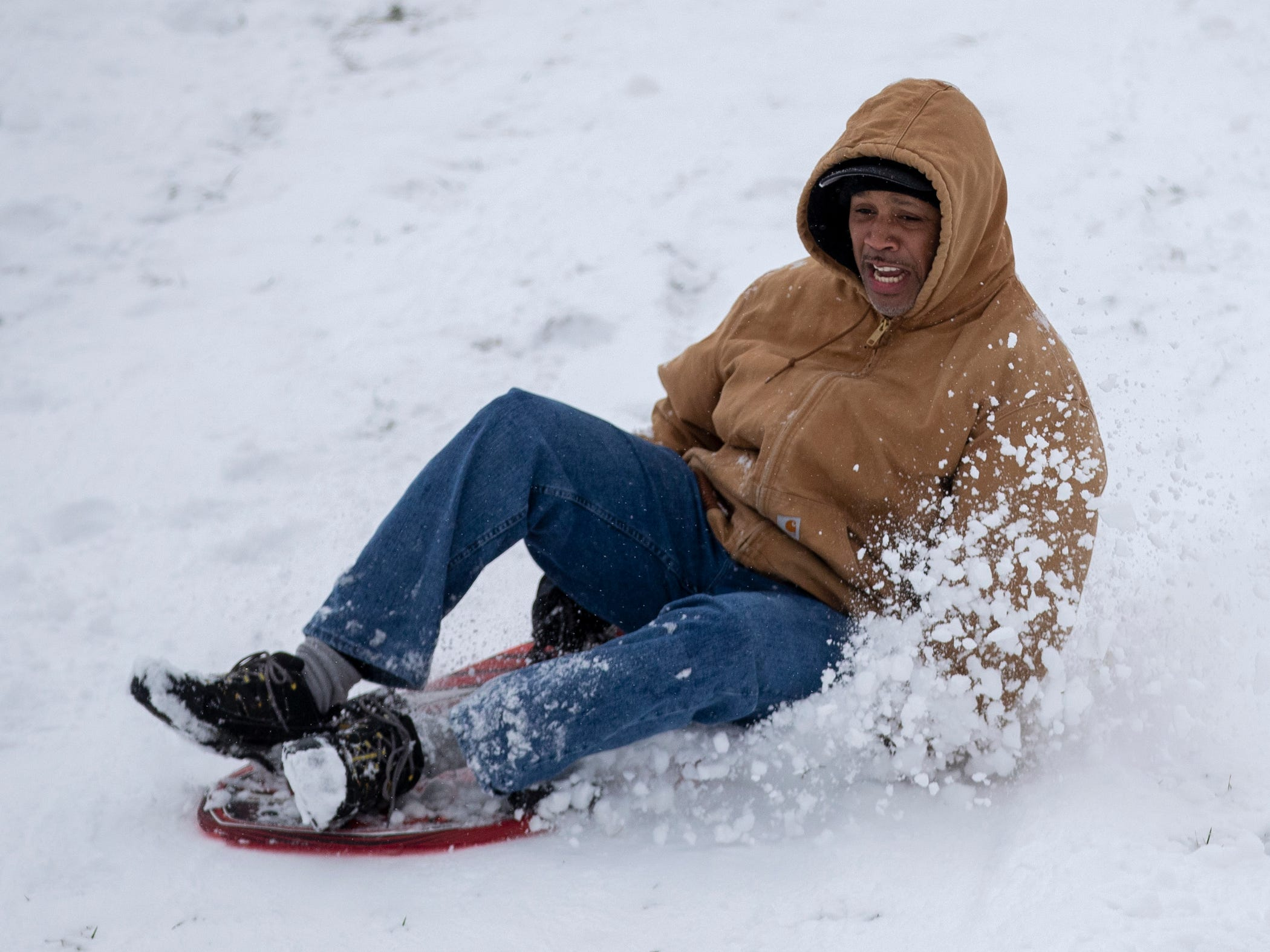 Damon Scott, 51, who'd brought his son and a friend to sled at Butler University, takes a run on a day where 5-7 inches of snow is expected to fall in Central Indiana, Indianapolis, Saturday, Jan. 12, 2019.