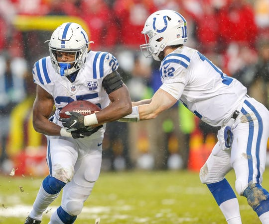 Indianapolis Colts running back Marlon Mack (25) takes the ball from quarterback Andrew Luck (12) against the Kansas City Chiefs in the second quarter at Arrowhead Stadium in Kansas City, Mo., on Saturday, Jan. 12, 2019.