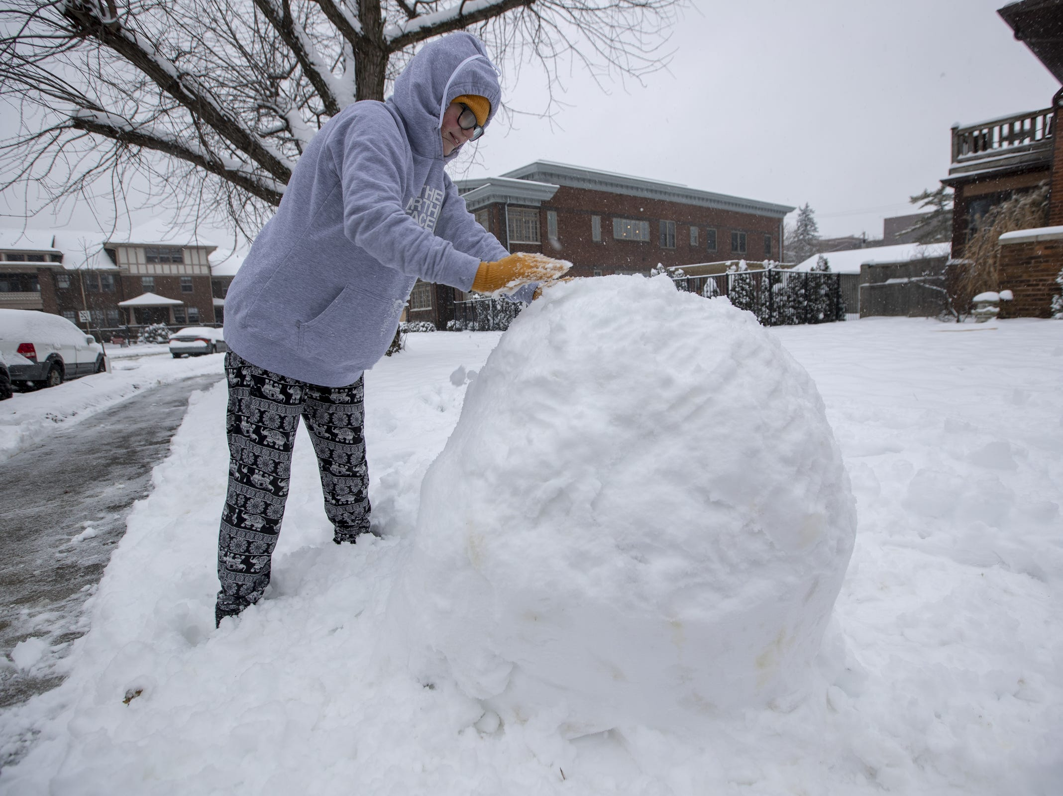 Madelin Senn, 12, works on making a snowman on a day where 5-7 inches of snow is expected to fall in Central Indiana, Indianapolis, Saturday, Jan. 12, 2019.