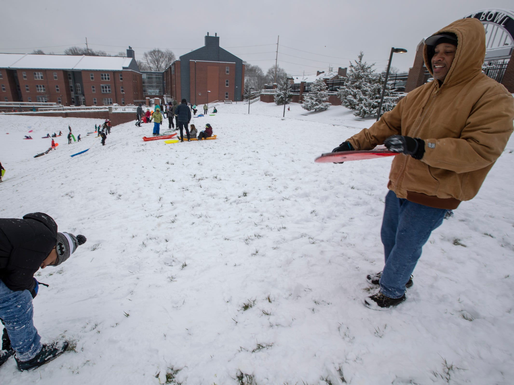 Damon Scott (right), joins a full house for sledding at the football stadium's hill at Butler University on a day where 5-7 inches of snow is expected to fall in Central Indiana, Indianapolis, Saturday, Jan. 12, 2019.