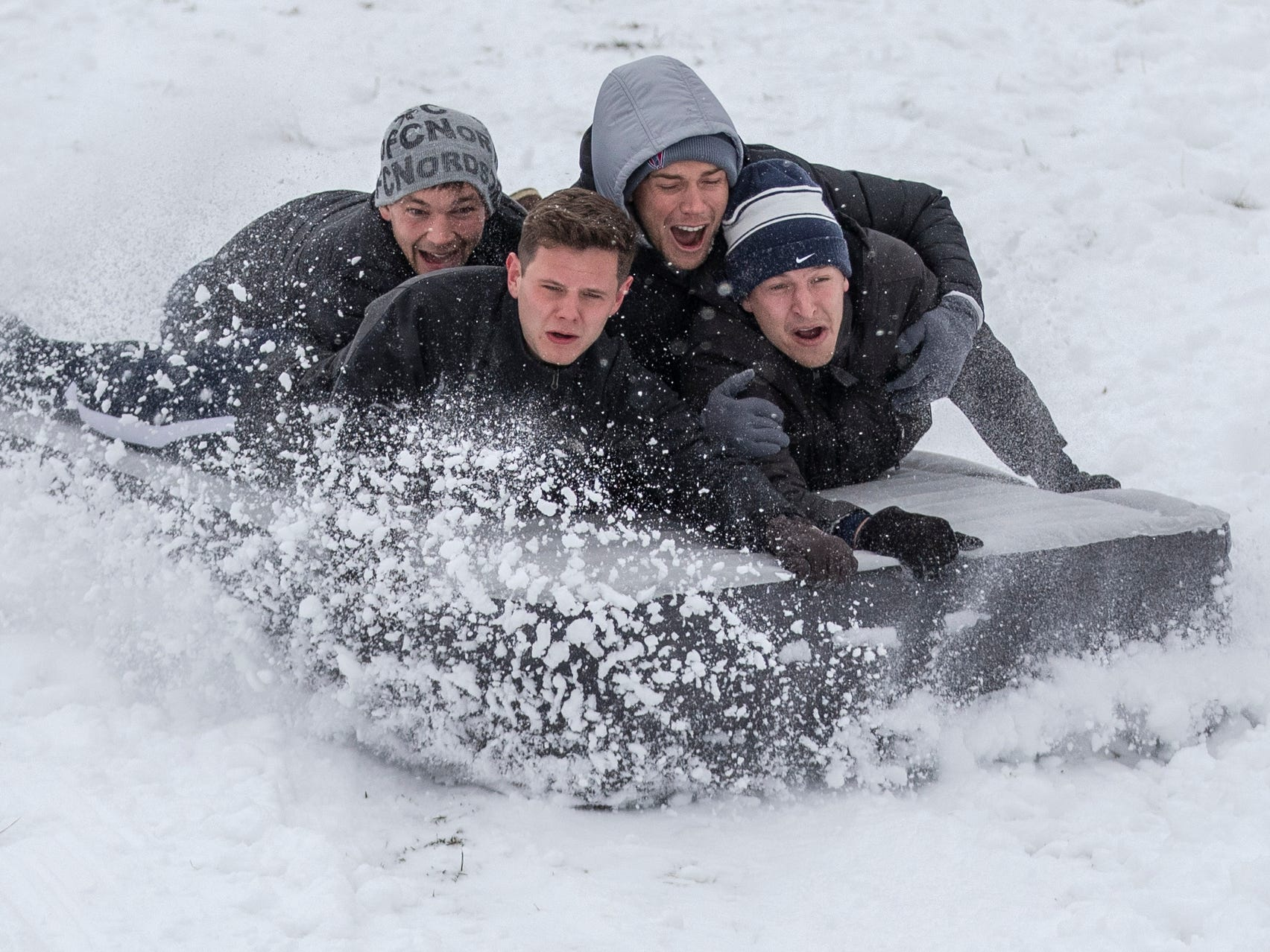 This group of four former Butler University students slide on an inflatable mattress at Butler University on a day where 5-7 inches of snow is expected to fall in Central Indiana, Indianapolis, Saturday, Jan. 12, 2019.