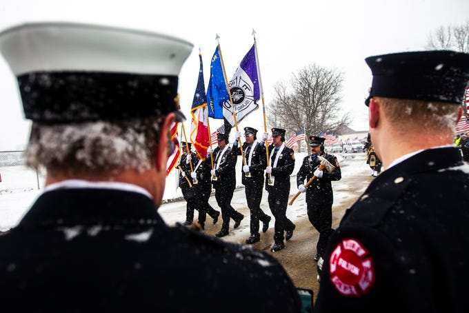 Firefighters line the road as members of the honor guard march by during a public memorial service for Lt. Eric Hosette on Saturday, Jan. 12, 2019, at Riverview Park Bandshell in Clinton, Iowa.
