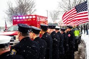Firefighters line the street as the procession approaches during a public memorial service for Lt. Eric Hosette on Saturday, Jan. 12, 2019, at Riverview Park Bandshell in Clinton, Iowa.