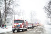 Firetrucks drive down the street in procession after the public memorial service for Lt. Eric Hosette on Saturday, Jan. 12, 2019, in Clinton, Iowa.