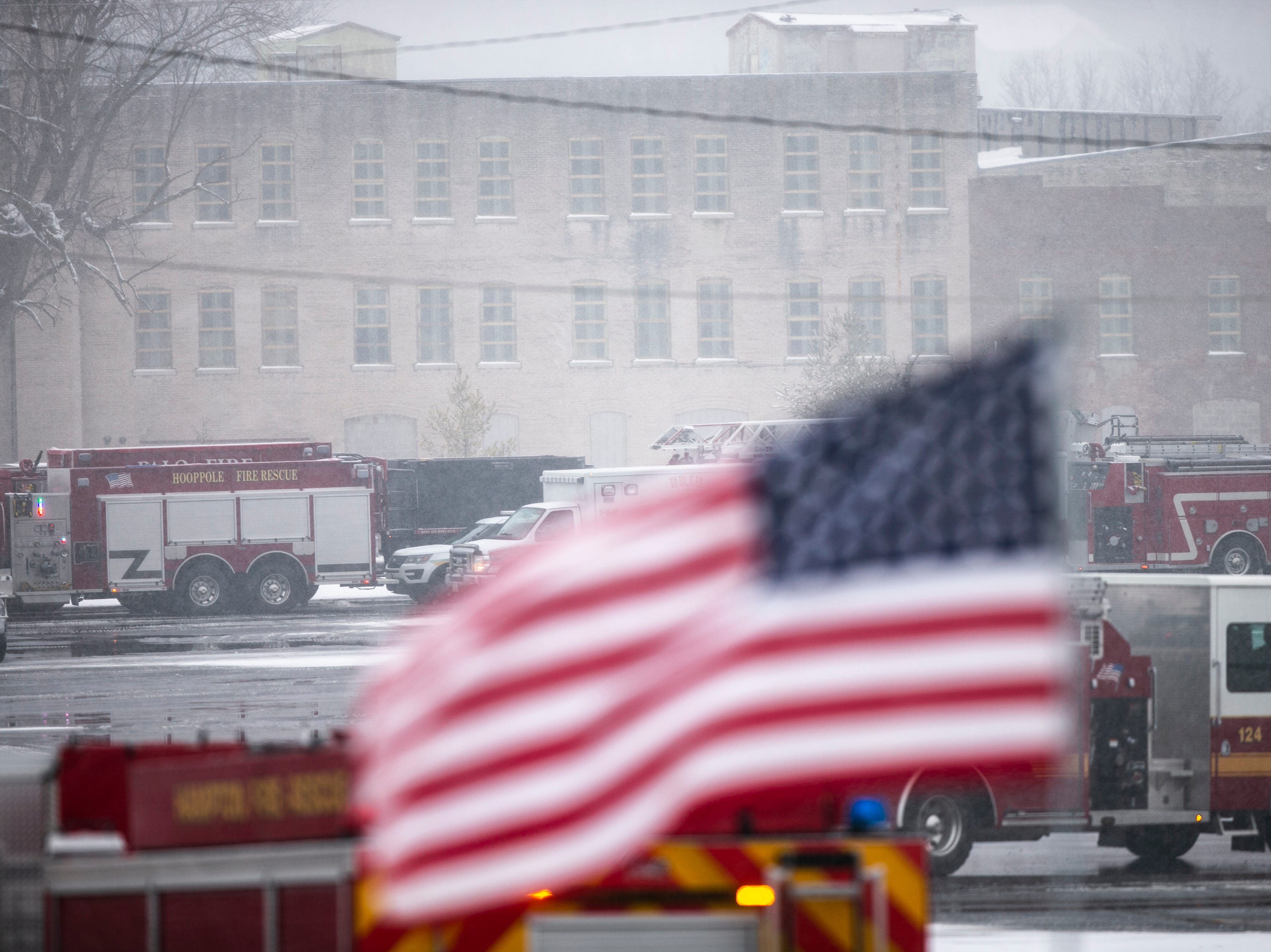 An American flag waves while firetrucks park during a public memorial service for Lt. Eric Hosette on Saturday, Jan. 12, 2019, at Riverview Park Bandshell in Clinton, Iowa.
