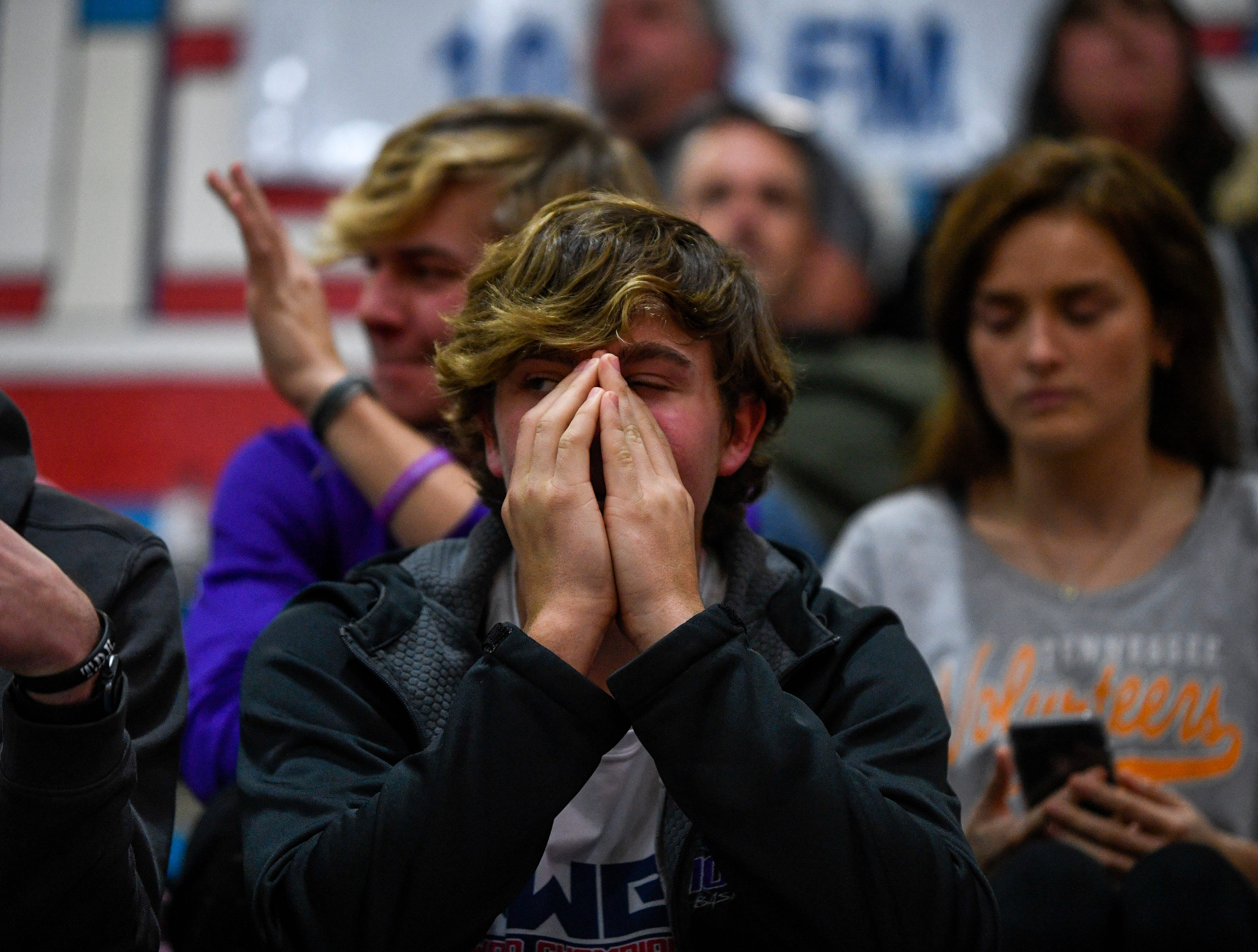 A TCA fan puts their hands over their mouth and opens one eye after Gibson County took possession during overtime in a TSSAA girls basketball game between Gibson County and Trinity Christian Academy at Gibson County High School in Dyer, Tenn., on Friday, Jan. 11, 2019.