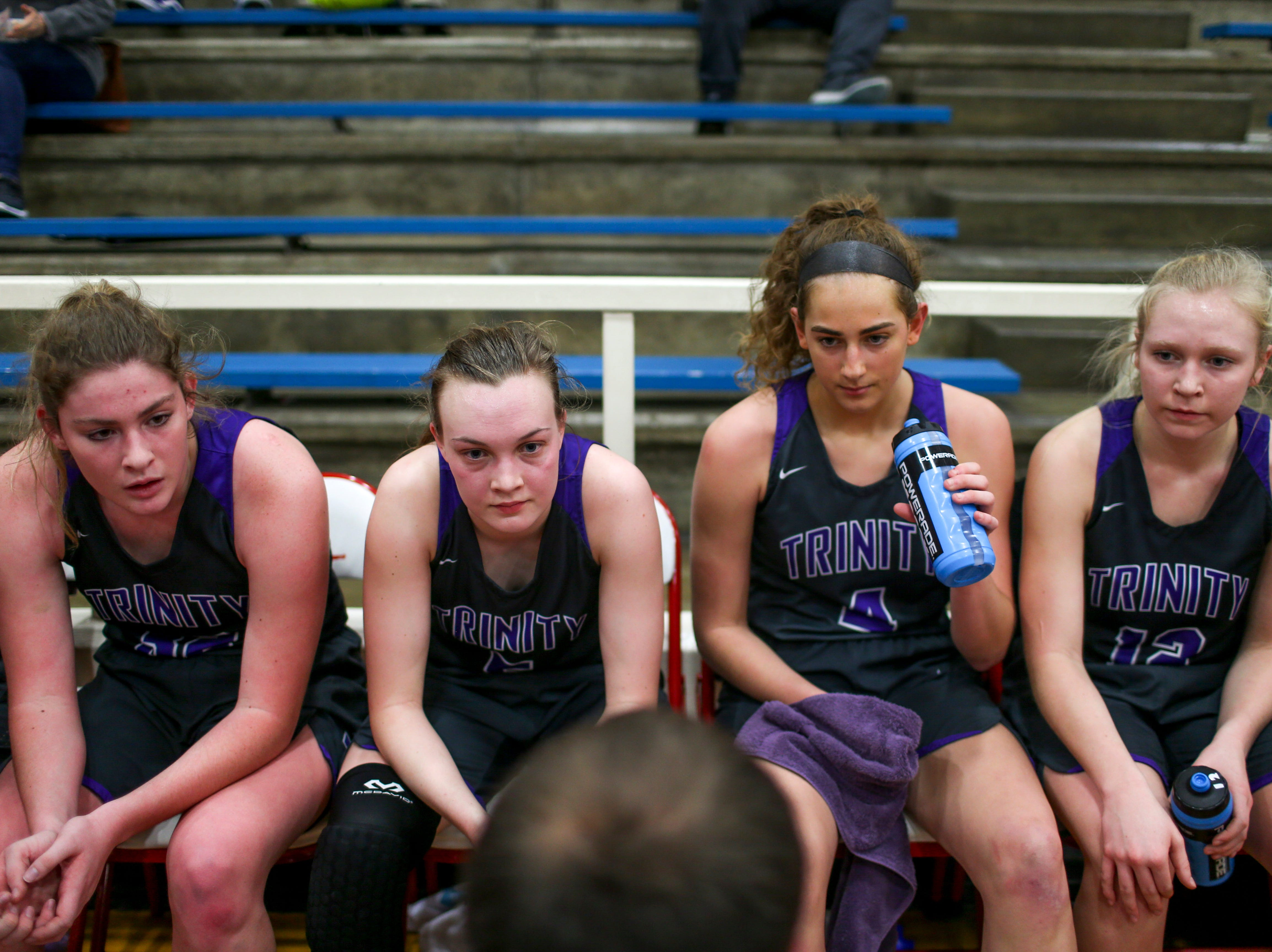 TCA players sit down and listen to head coach Matthew Coble during a timeout in a TSSAA girls basketball game between Gibson County and Trinity Christian Academy at Gibson County High School in Dyer, Tenn., on Friday, Jan. 11, 2019.