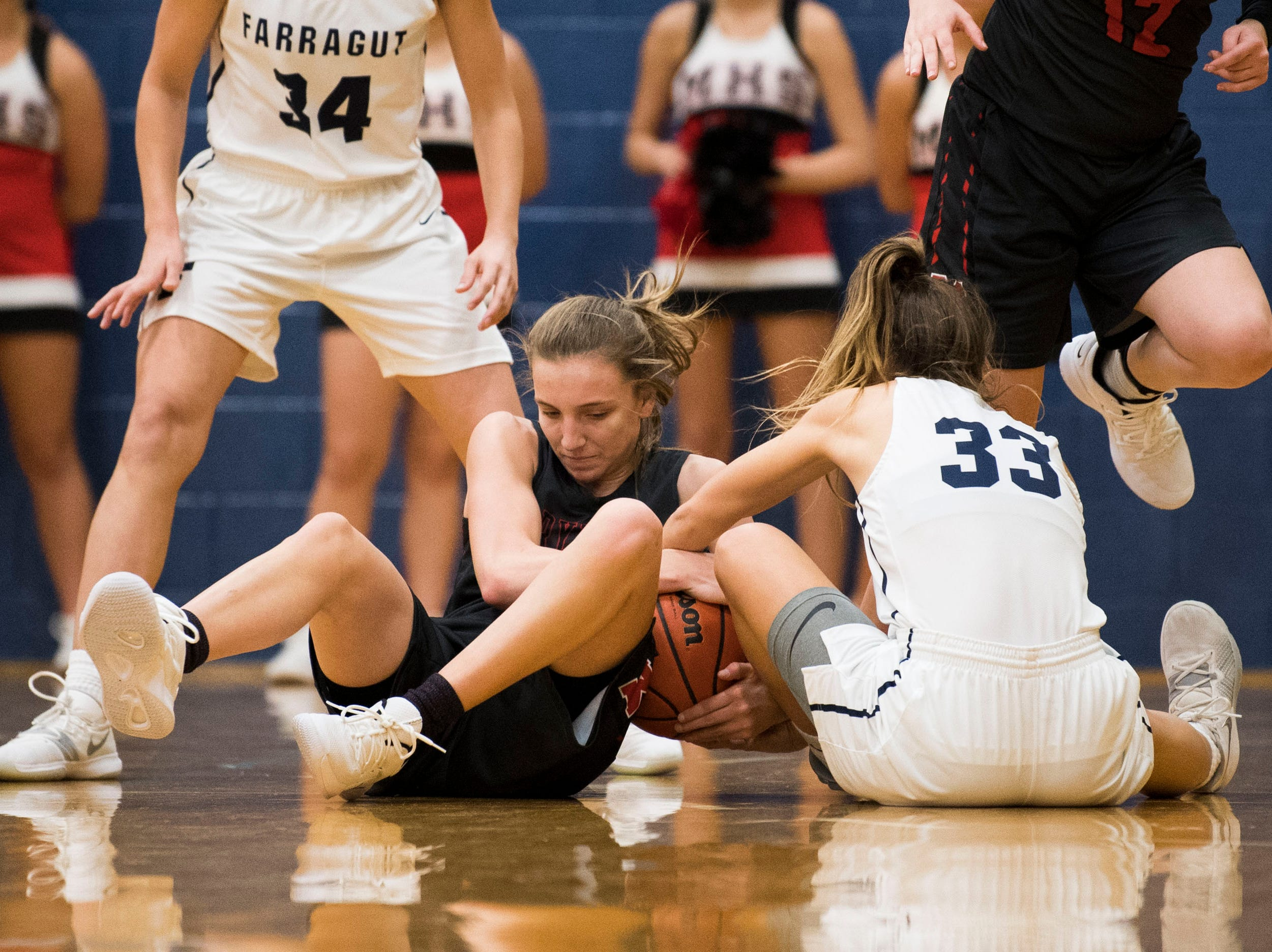 Farragut's Sydney Chapman (33) and a Maryville player fight for possession during a high school basketball game between Maryville and Farragut at Farragut, Friday, Jan. 11, 2019.