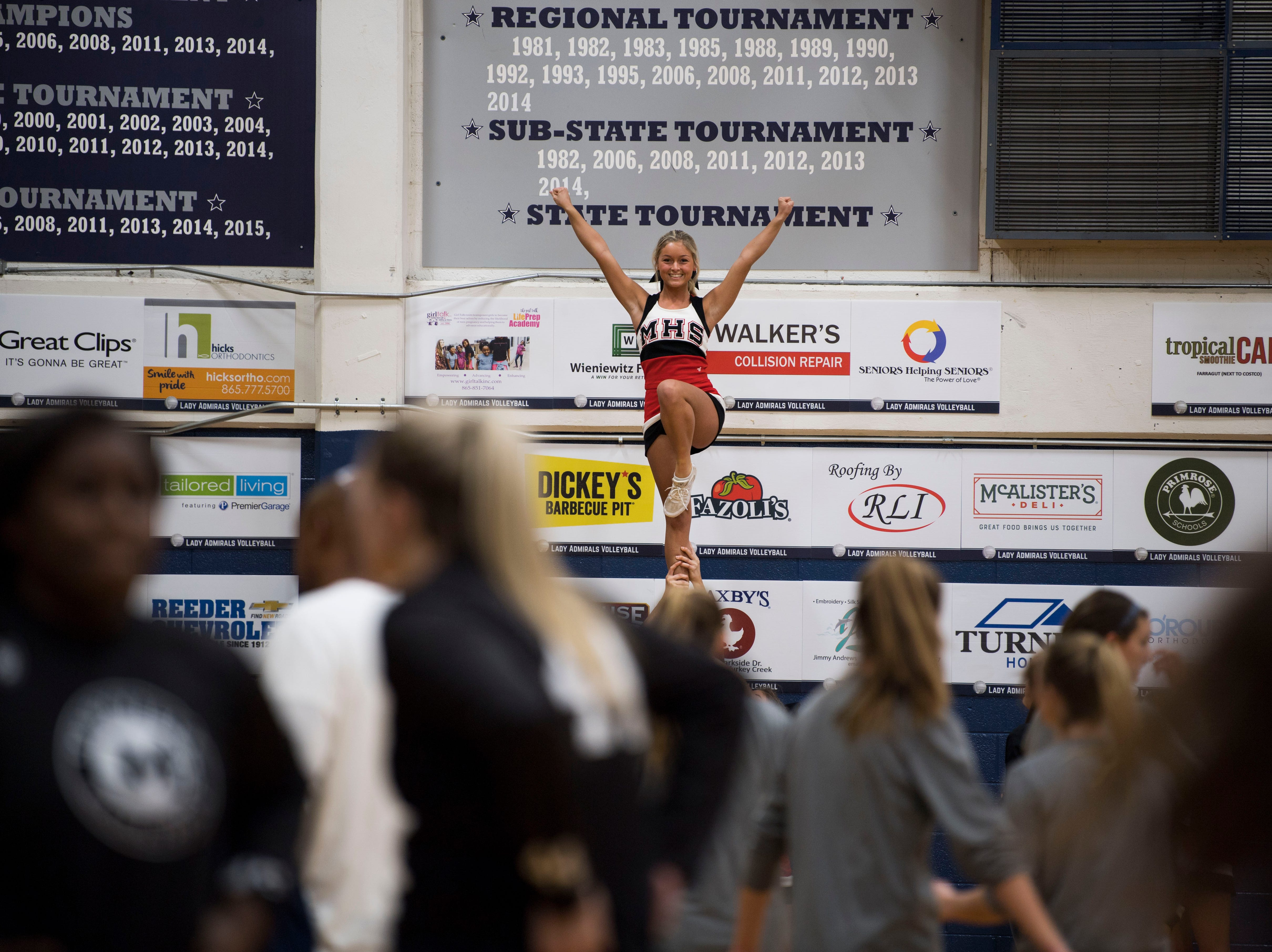 A Maryville cheerleader rises above the crowd before a high school basketball game between Maryville and Farragut at Farragut, Friday, Jan. 11, 2019.