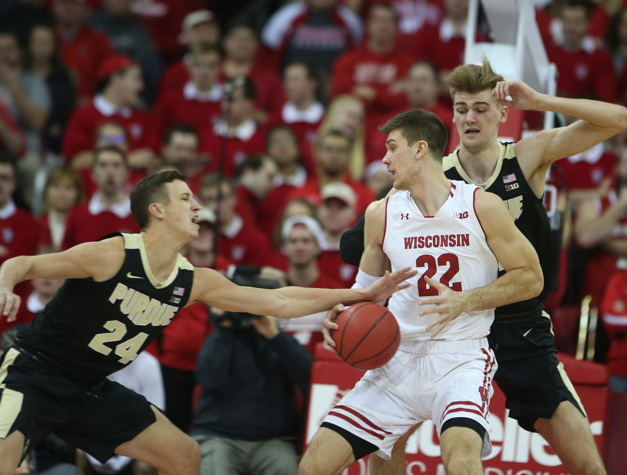 Jan 11, 2019; Madison, WI, USA; Wisconsin Badgers forward Ethan Happ (22) looks to pass as Purdue Boilermakers forward Grady Eifert (24) and forward Matt Haarms (right) defend during the first half at the Kohl Center. Mandatory Credit: Mary Langenfeld-USA TODAY Sports