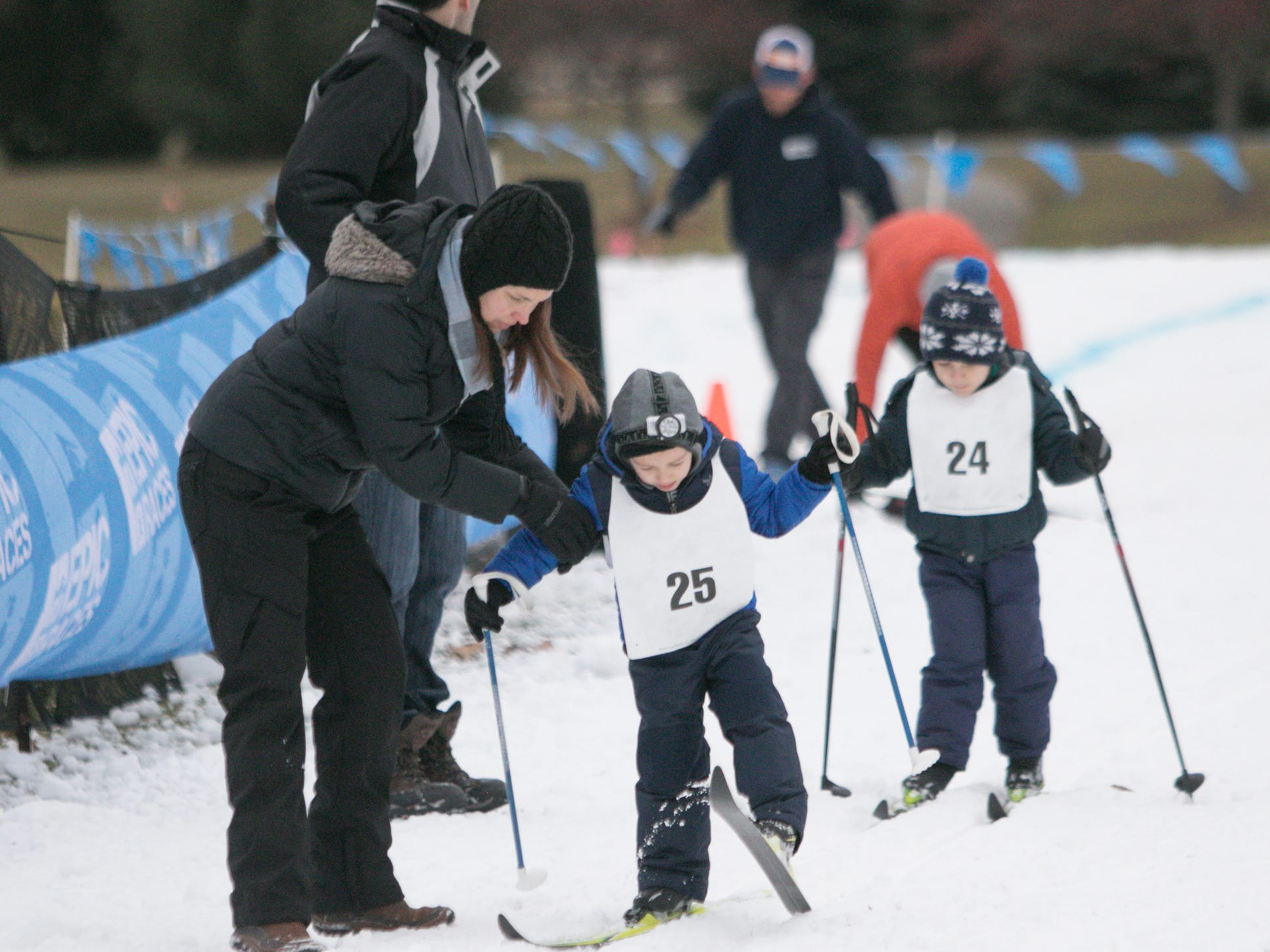 Jodie Haberkorn assists Beckham Haberkorn, no. 25, as Greg Ehinger accompanies son Vincent in the Frosty Ski Fest Saturday, Jan. 12, 2019.