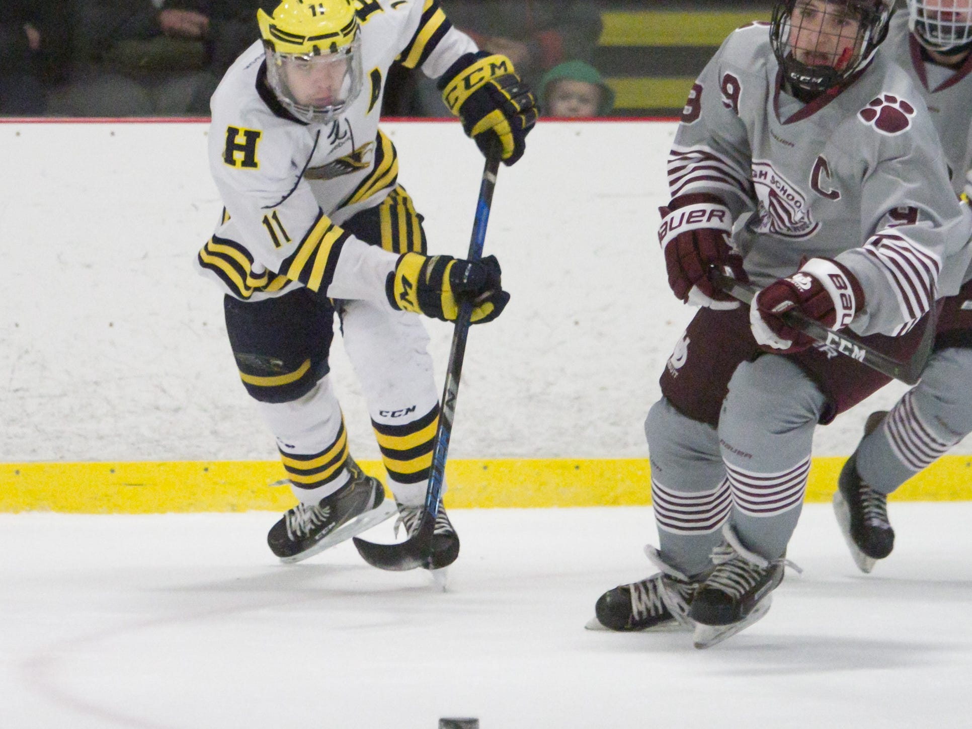 Hartland's Gabe Anderson (11), who scored the winning goal, races Detroit U of D Jesuit's Ben Charboneau for the puck on Friday, Jan. 11, 2019.