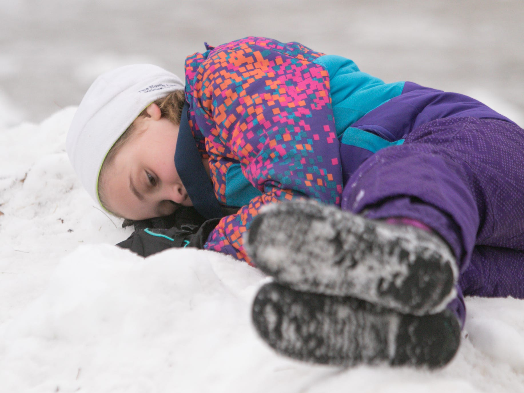 8-year-old Logan Anderson of Grand Rapids rests on a hill of man-made snow on the side of the race course, having participated in the Frosty Ski Fest kids' race Saturday, Jan. 12, 2019.