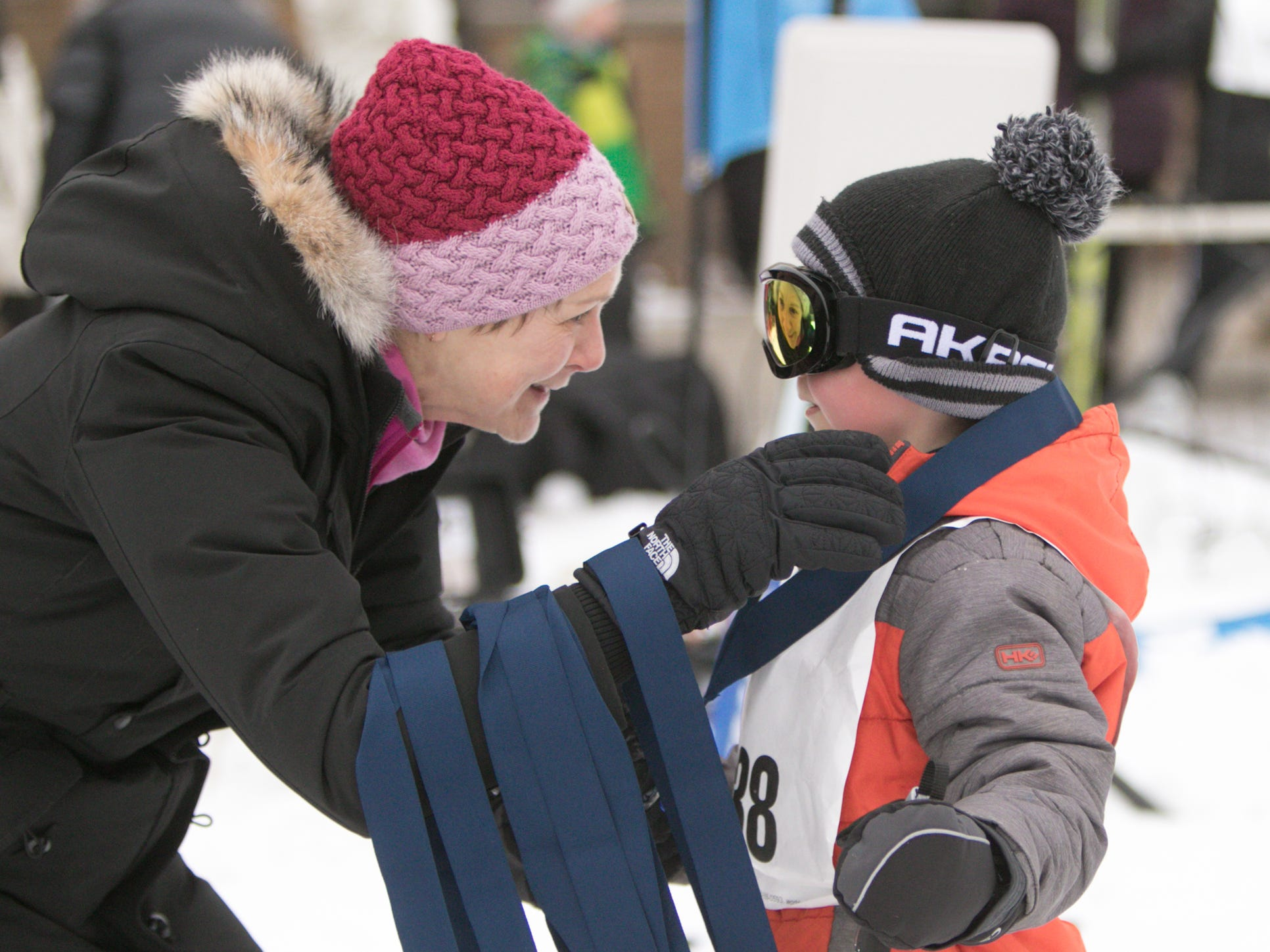 Volunteer Amy Kostrzewa, with Team NordicSkiRacer, presents 7-year-old Lukas Ries of Brighton with a ribbon, as each of the children in the Frosty Ski Fest kids' race gets honored upon completing 30 minutes of skiing Saturday, Jan. 12, 2019.