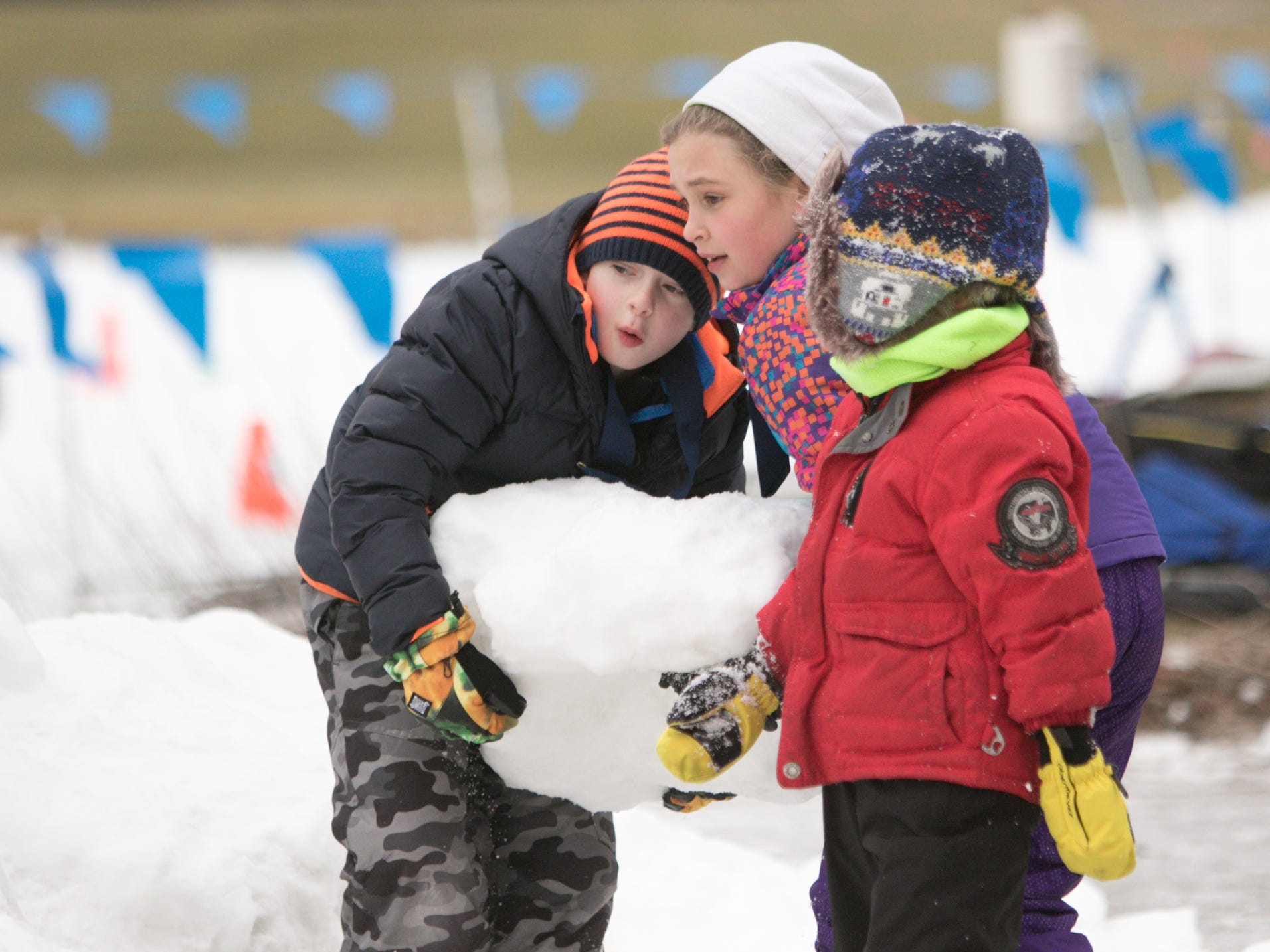 After the Frosty Ski Fest kids' race Saturday, Jan. 12, 2019, from left, Alex Ries, nine years old, Logan Anderson, eight, and 5-year-old brother Graeme Anderson play with some of the man-made snow provided for the ski events at Huron Meadows.