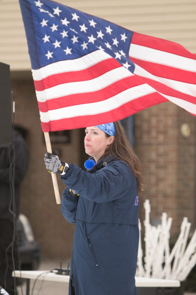 Jenn Beams of Epic Races holds the American flag as the National Anthem is sung before the 15k heat of the Frosty Freestyle race Saturday, Jan. 12, 2019.