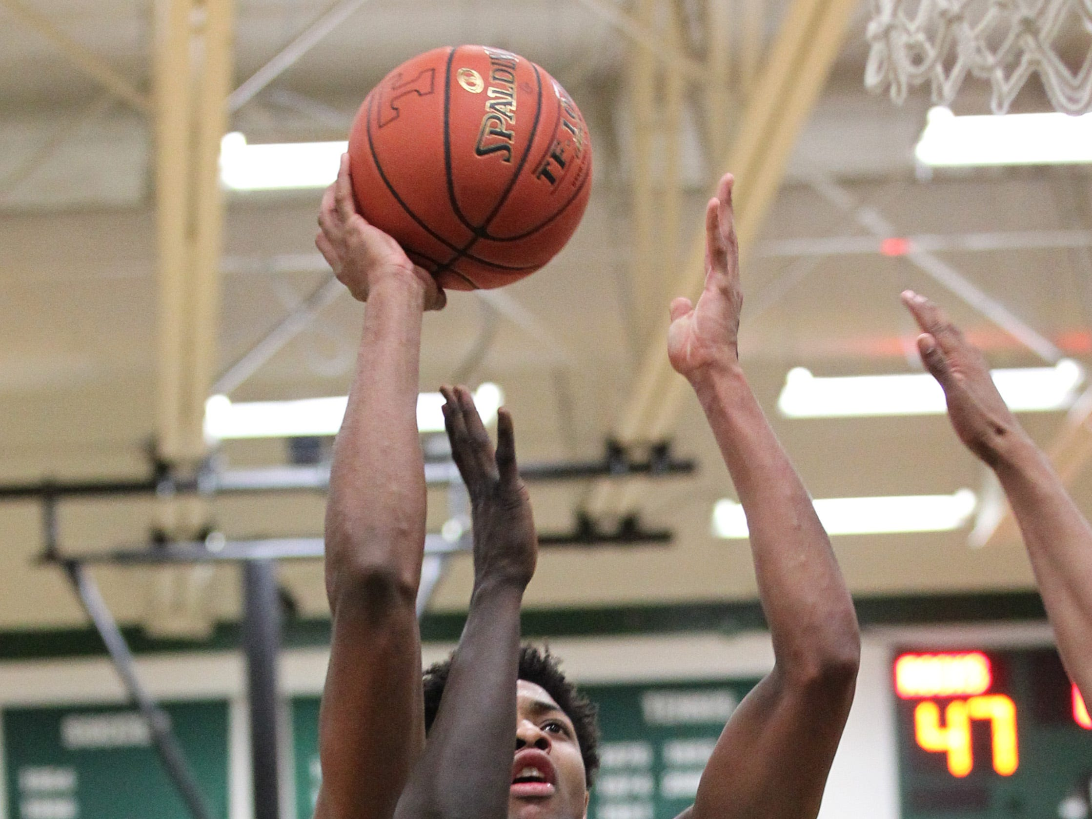 Trinity High School's David Johnson (13) fights to get his shot off under pressure from Waggener High School's Jaago Kalakon (10) during the second half of play at Trinity High School on Jan. 11, 2019.
