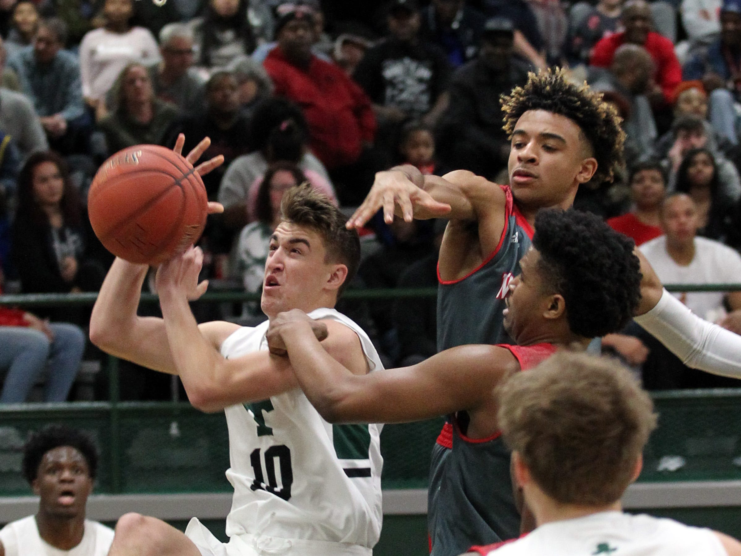 Trinity High School's Kamari Kenemore (14) fights to get his shot off under pressure from Waggener High School's Kameron Barnett (1) during the first half of play at Trinity High School in Louisville, Kentucky, Jan. 11,  2019.