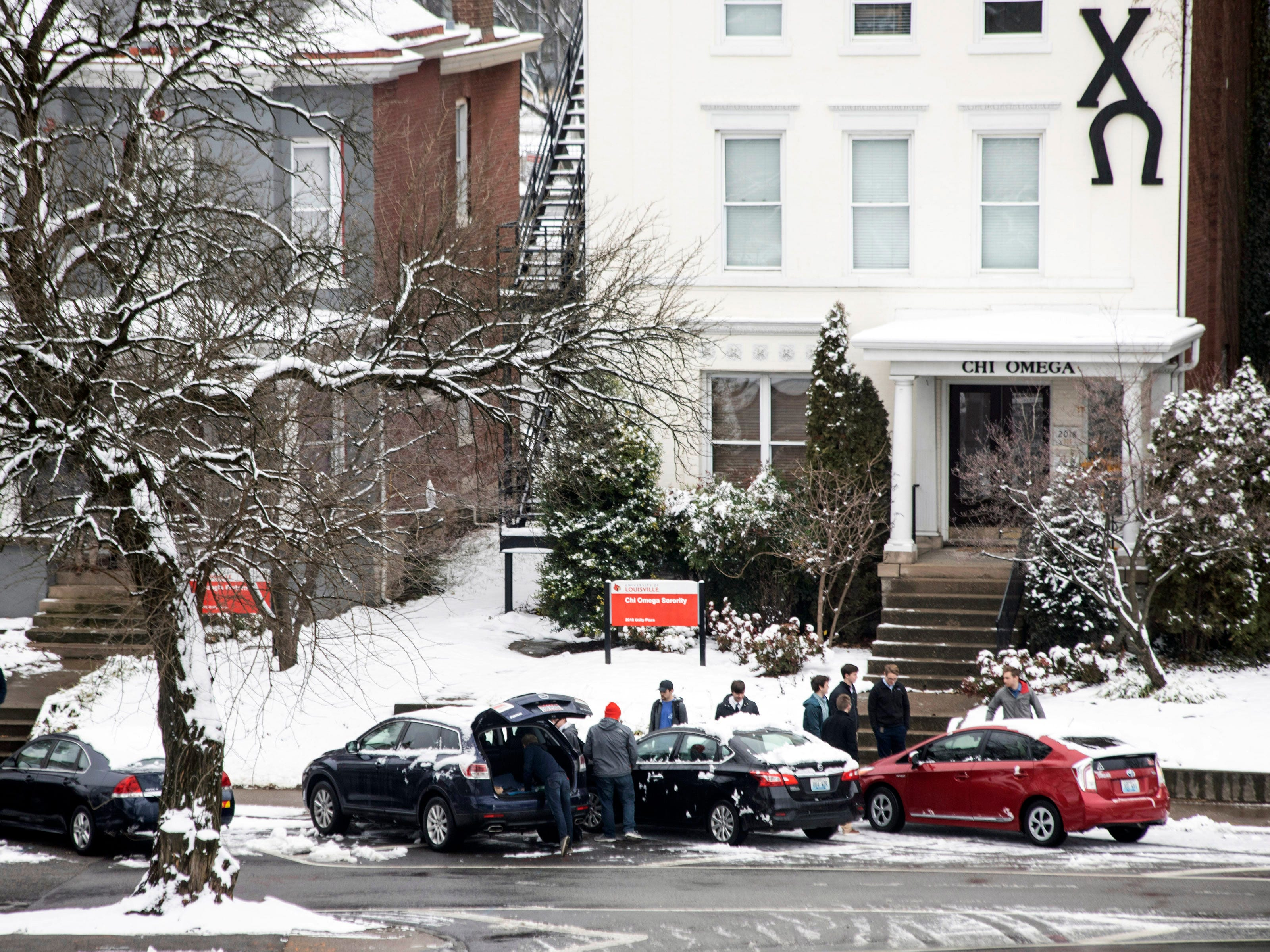 University of Louisville students clear off cars after a late night snowfall blanketed Louisville for the first time in 2019. 1/12/19