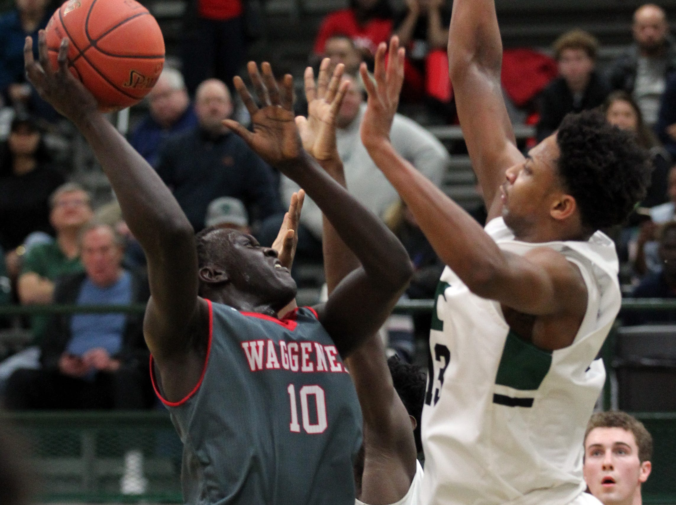 Waggener High School's Jaago Kalakon (10) fights to get his shot off under pressure from Trinity High School's David Johnson (13) during the second half of play at Trinity High School on Jan. 11,  2019.