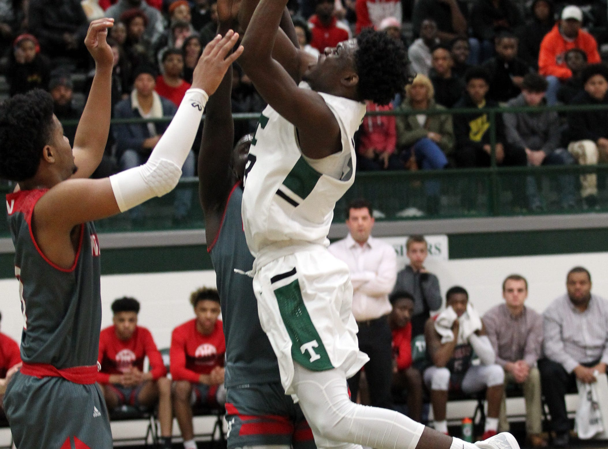Trinity High School's Jamil Hardaway (23) fights to get his shot off under pressure from Waggener High School's Dallas Rufus (3) during the first half of play at Trinity High School in Louisville, Kentucky, Jan. 11,  2019.