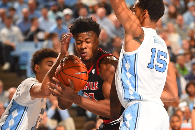 Louisville Cardinals center Steven Enoch (23) fights for the ball with North Carolina Tar Heels guard Cameron Johnson (13) and forward Garrison Brooks (15) in the first half at Dean E. Smith Center in Chapel Hill, North Carolina, on Saturday, Jan. 12, 2019.