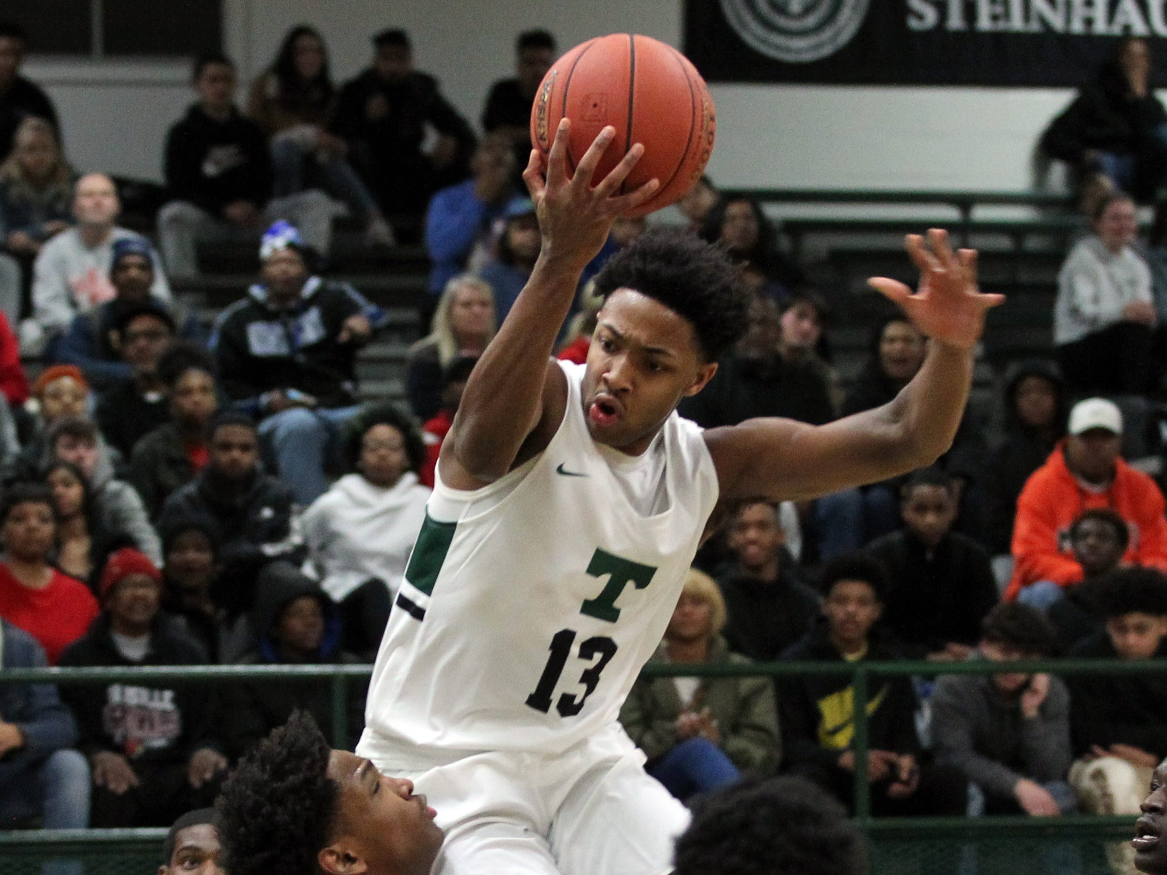 Trinity High School's David Johnson (13) fights for the rebound with Waggener High School's defense  during the first half of play at Trinity High School in Louisville, Kentucky, Jan. 11,  2019.