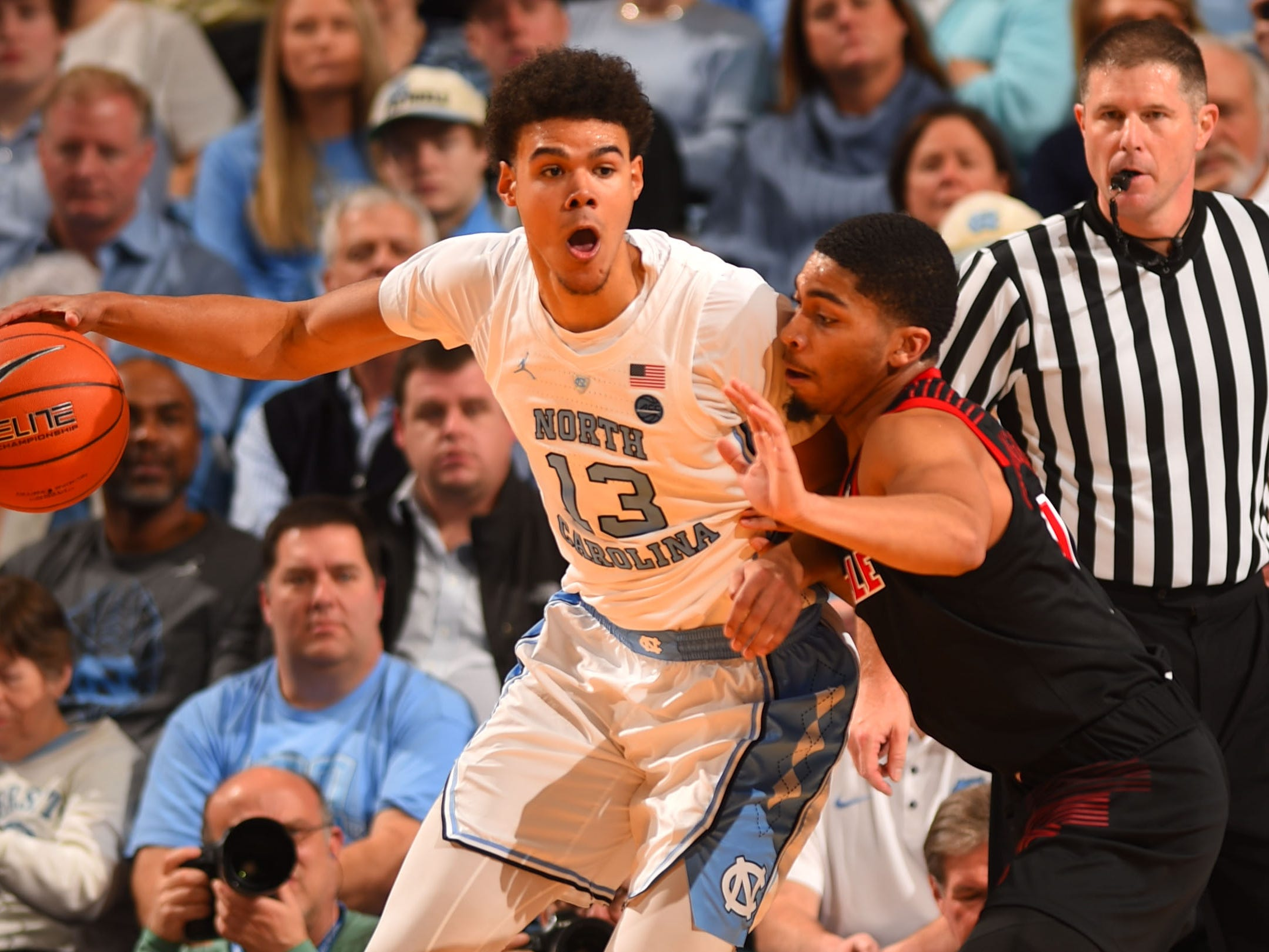 North Carolina Tar Heels guard Cameron Johnson (13) with the ball as Louisville Cardinals guard Christen Cunningham (1) defends at Dean E. Smith Center in Chapel Hill, North Carolina, on Saturday, Jan. 12, 2019.
