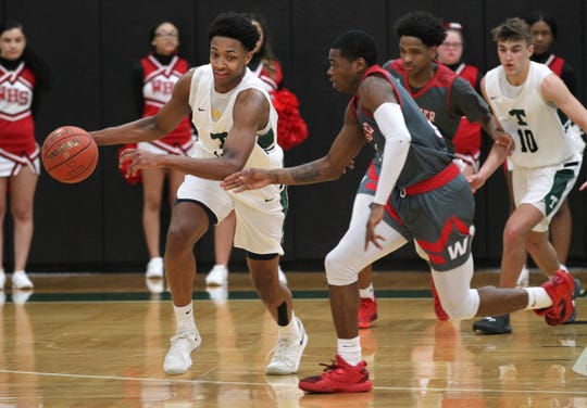 Trinity High School's David Johnson (13) fights pressure from Waggener High School's Kevion Hudson (5) during the first half of play at Trinity High School on Jan. 11, 2019.