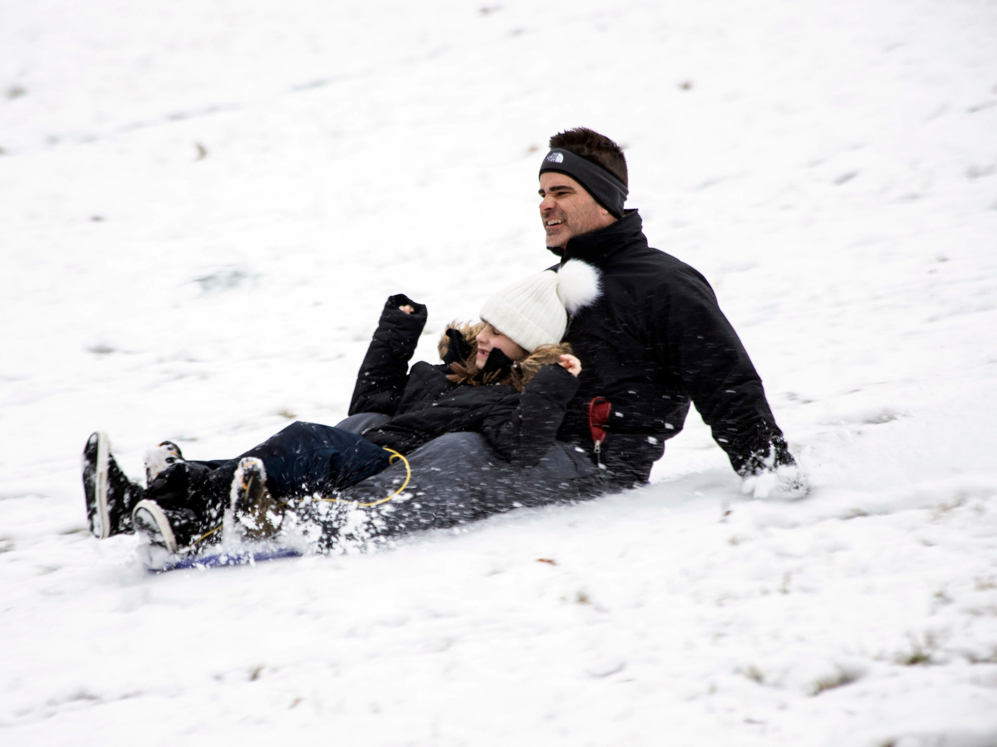 Josh and Elise Myers pick up speed while sledding down Baringer Hill (ak Dog Hill) in Cherokee Park on Saturday morning. 1/12/19