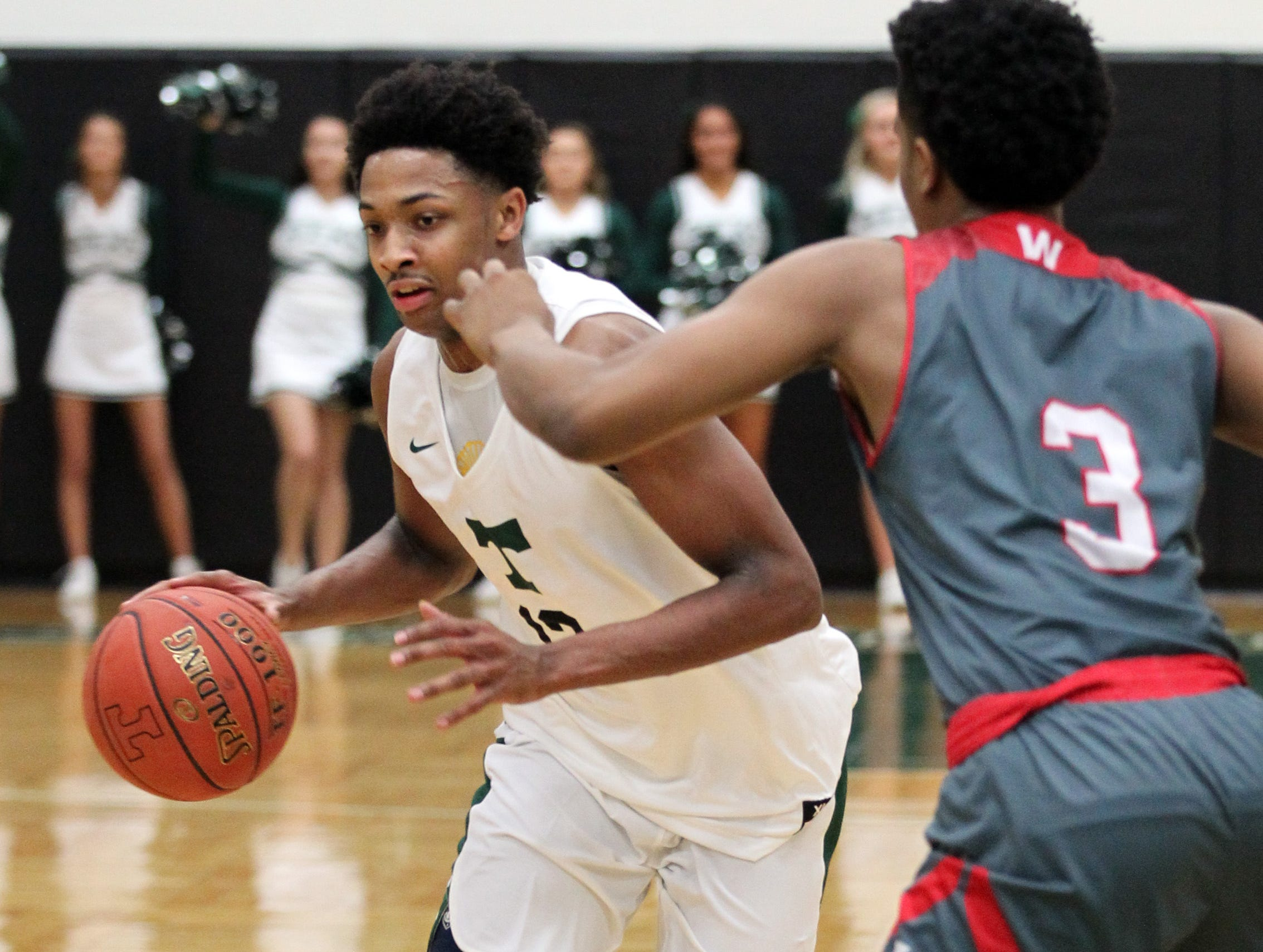 Trinity High School's David Johnson (13) fights pressure from Waggener High School's Dallas Rufus (3) during the first half of play at Trinity High School on Jan. 11,  2019.