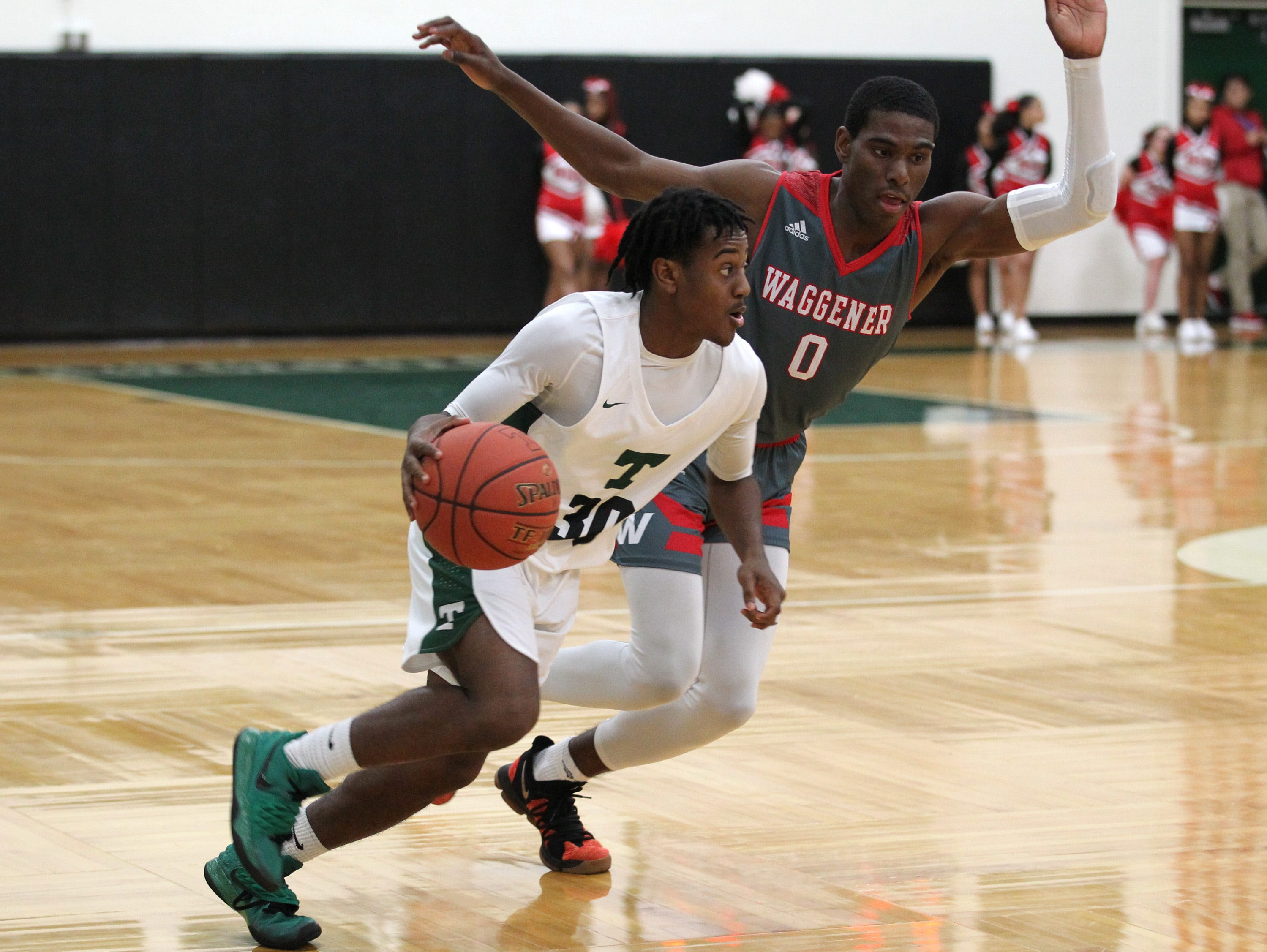 Trinity High School's Wynton Johnson (30) fights pressure from Waggener High School's Cobie Montgomery (0) during the second half of play at Trinity High School on Jan. 11, 2019.