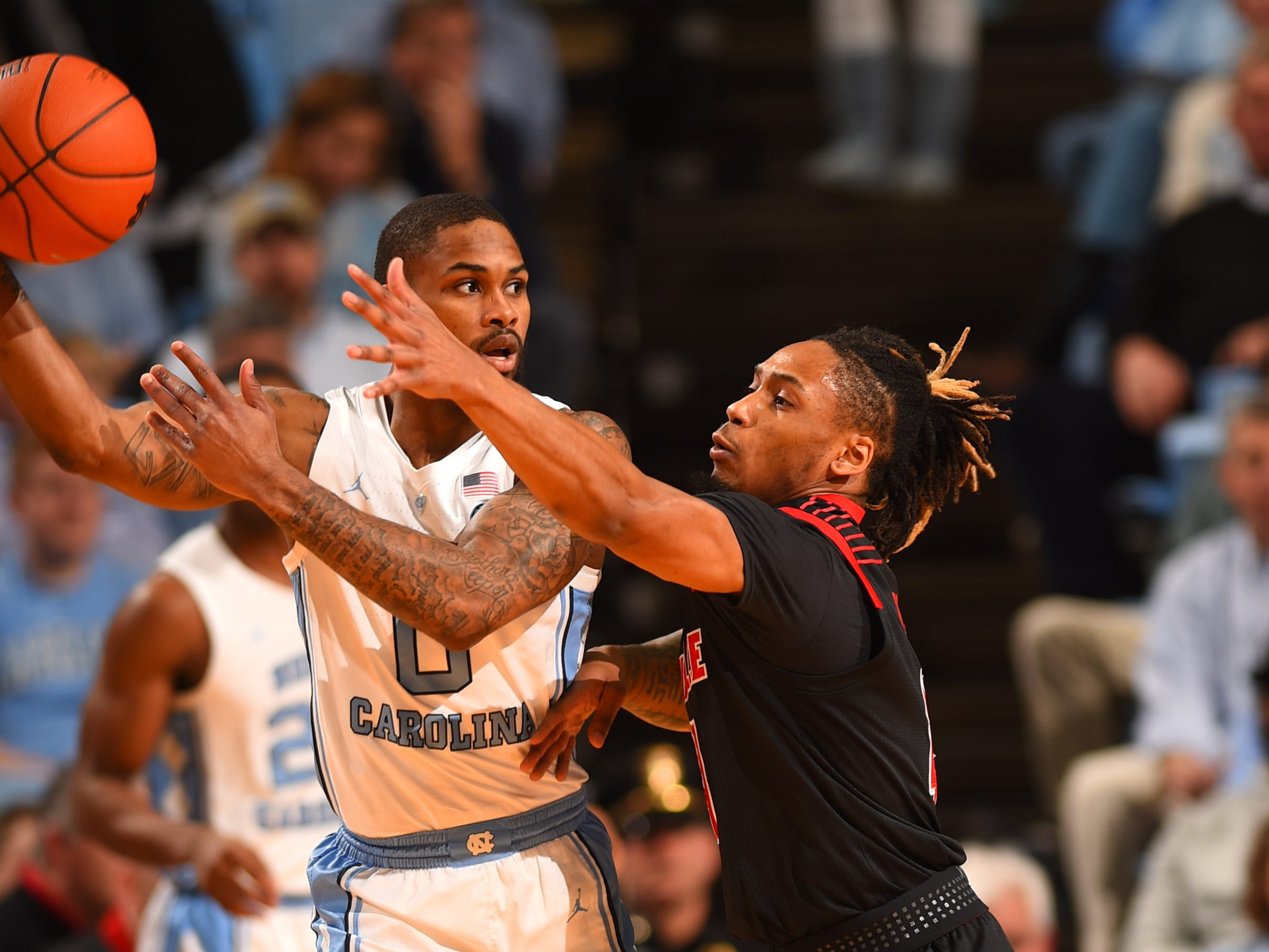 North Carolina Tar Heels guard Seventh Woods (0) with the ball as Louisville Cardinals guard Khwan Fore (4) defends in the first half at Dean E. Smith Center in Chapel Hill, North Carolina, on Saturday, Jan. 12, 2019.