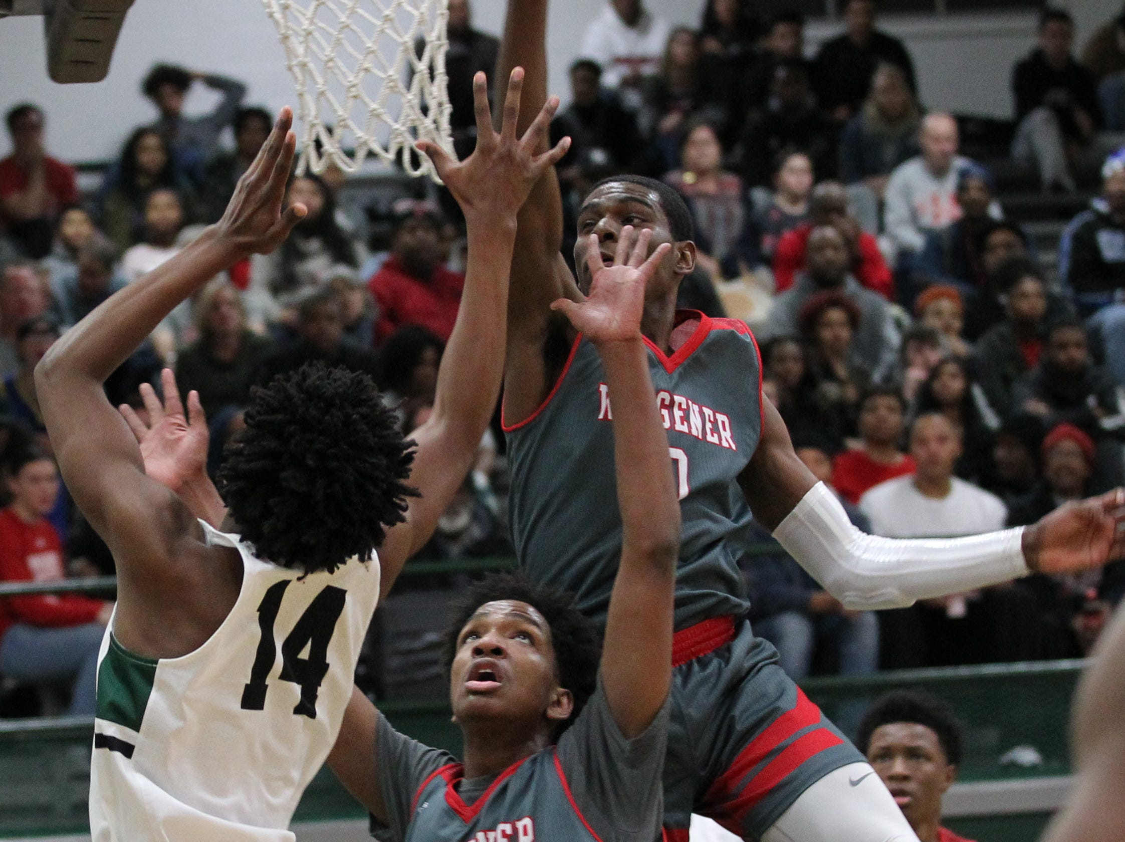 Trinity High School's Kamari Kenemore (14) fights to get his shot off under pressure from Waggener High School's Cobie Montgomey (0) and Nicholas Brewer (14) during the first half of play at Trinity High School in Louisville, Kentucky, Jan. 11,  2019.
