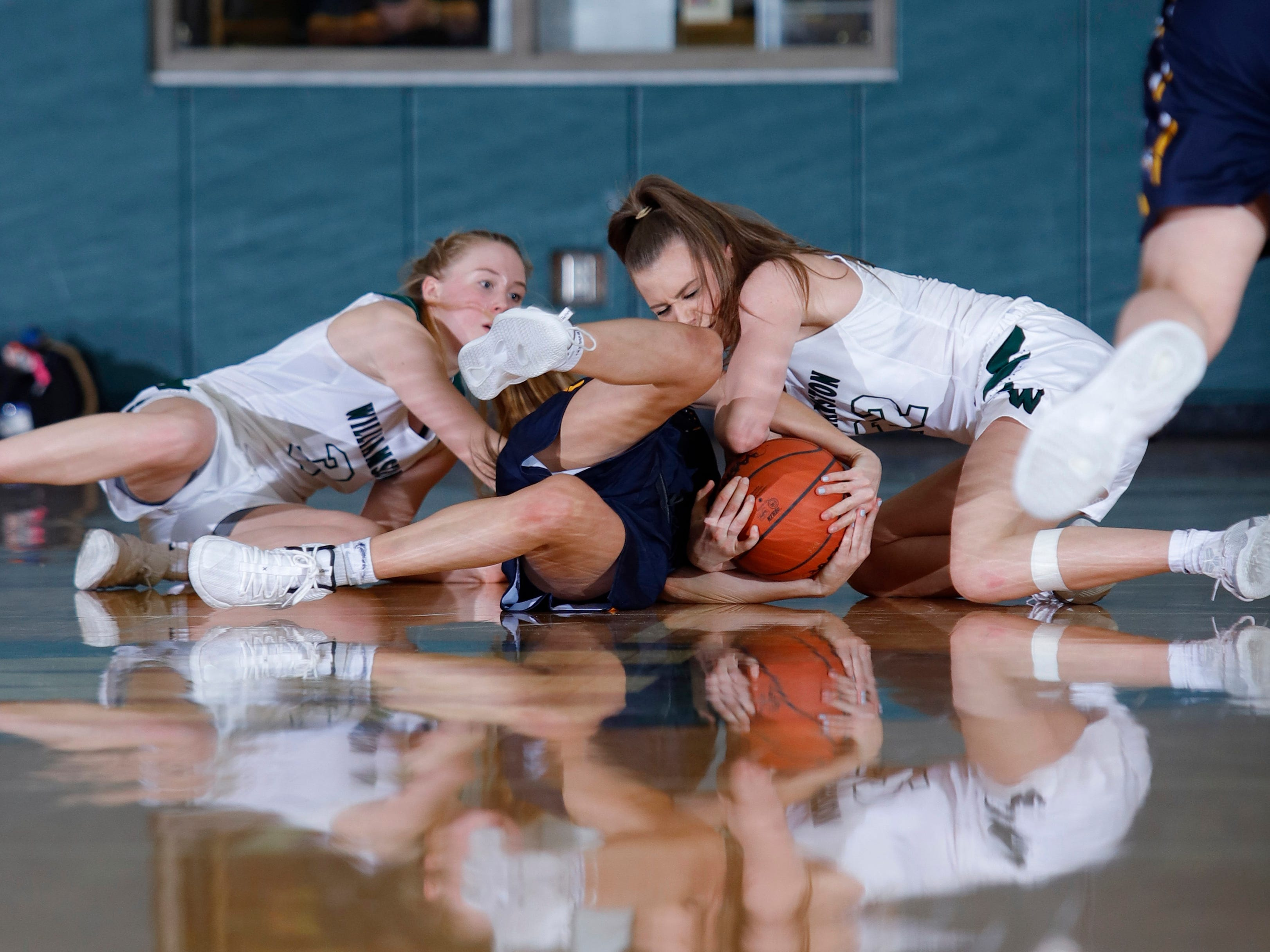 Haslett's Brenna Bailey, center, and Williamston's Kenzie Lewis, right, and Allie Sherrer wrestle for the ball, Friday, Jan. 11, 2019, in Williamston, Mich.
