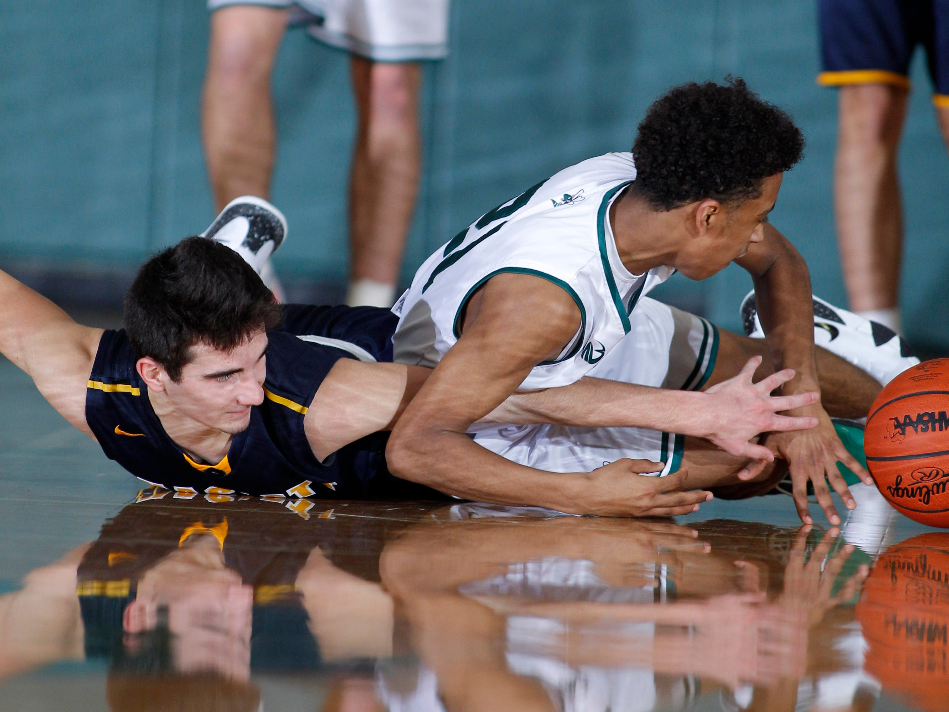 Williamston's Mason Docks, right, and Haslett's Mitchell Mowid battle for the ball, Friday, Jan. 11, 2019, in Williamston, Mich.