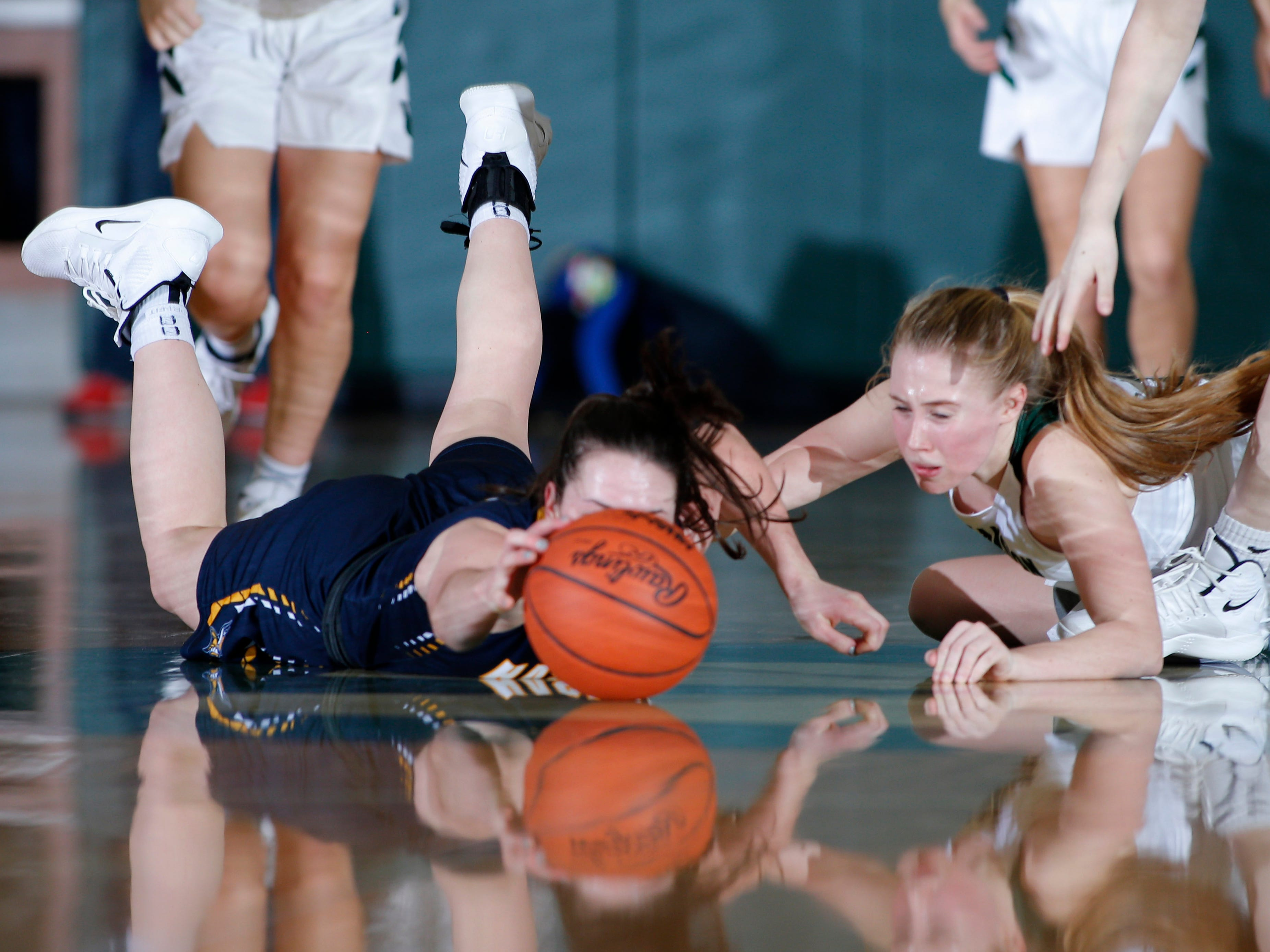 Haslett's Ella McKinney, left, and Williamston's Allie Sherrer dive for the ball, Friday, Jan. 11, 2019, in Williamston, Mich.